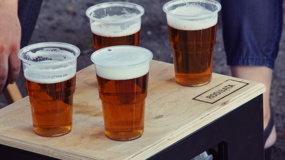 four clear plastic disposable cups with beer on the top of the board