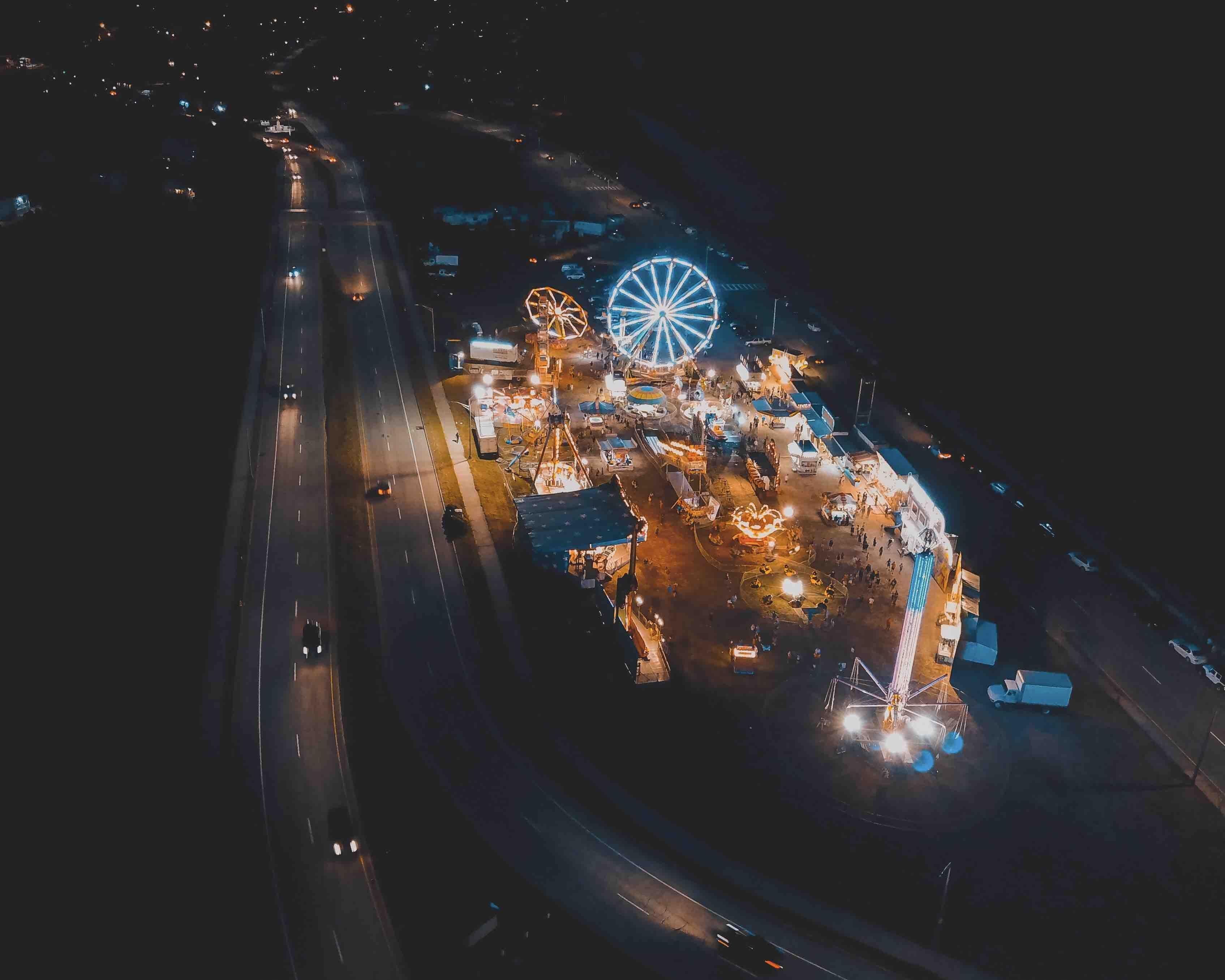 concrete roads with cars passing near amusement park