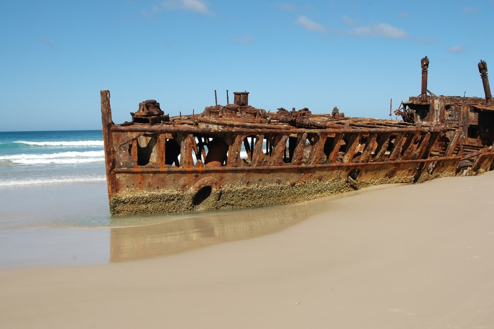 ship wreck docked on beach during day time