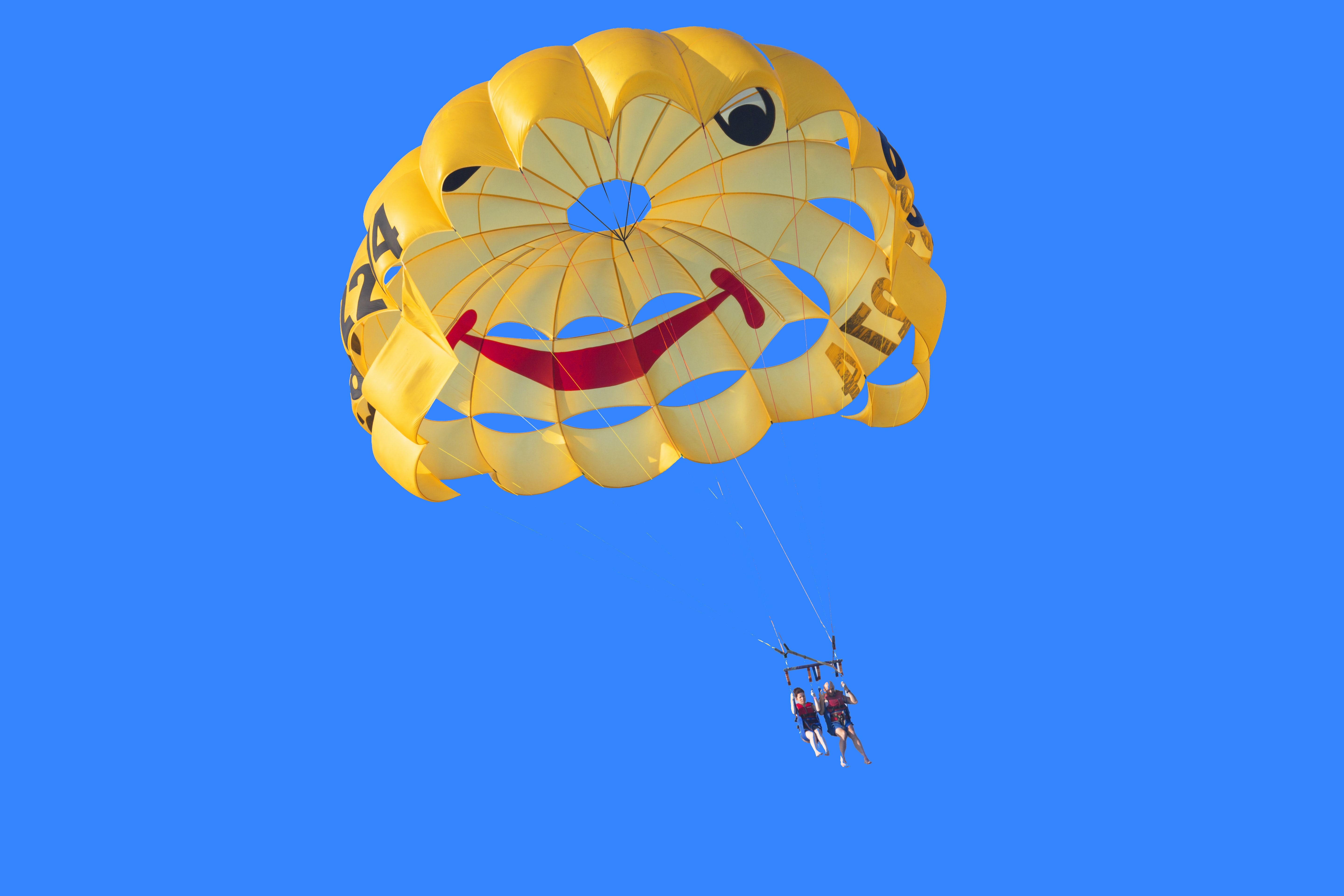 People parachuting across a blue sky with a yellow smiley face parachute