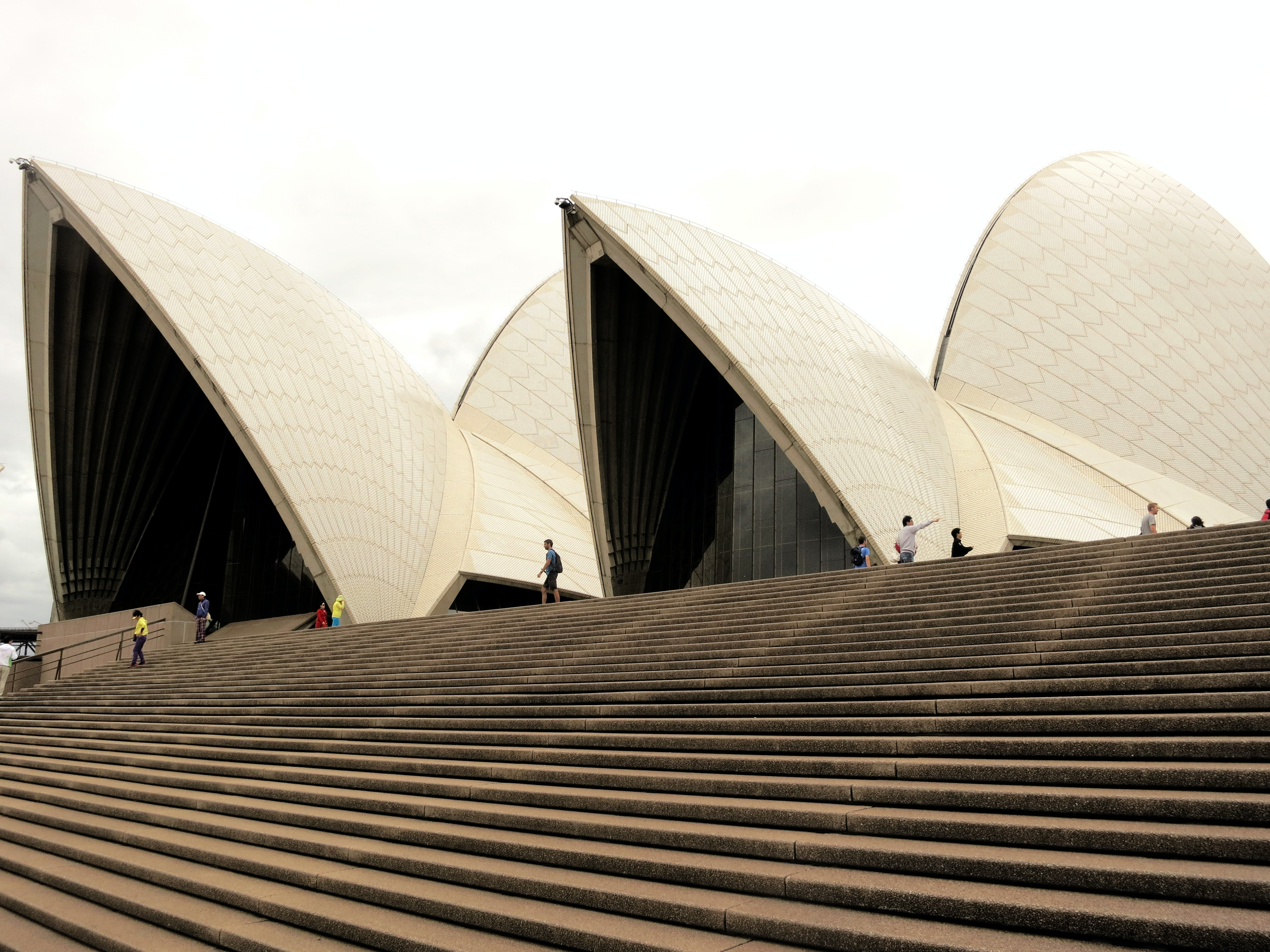 Shot of the steps to the Sydney Opera House where tourists are walking around under an overcast sky