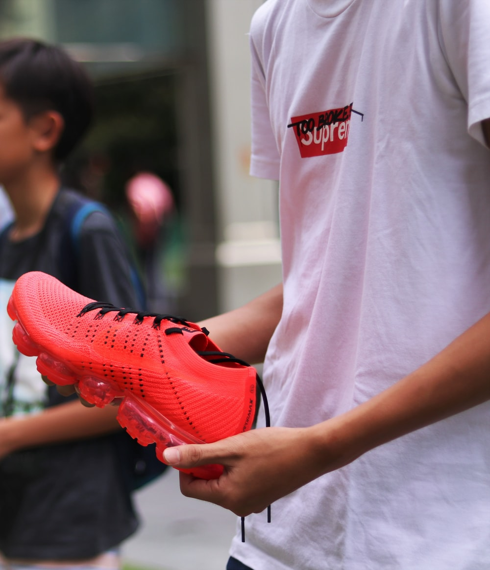person holding red shoe
