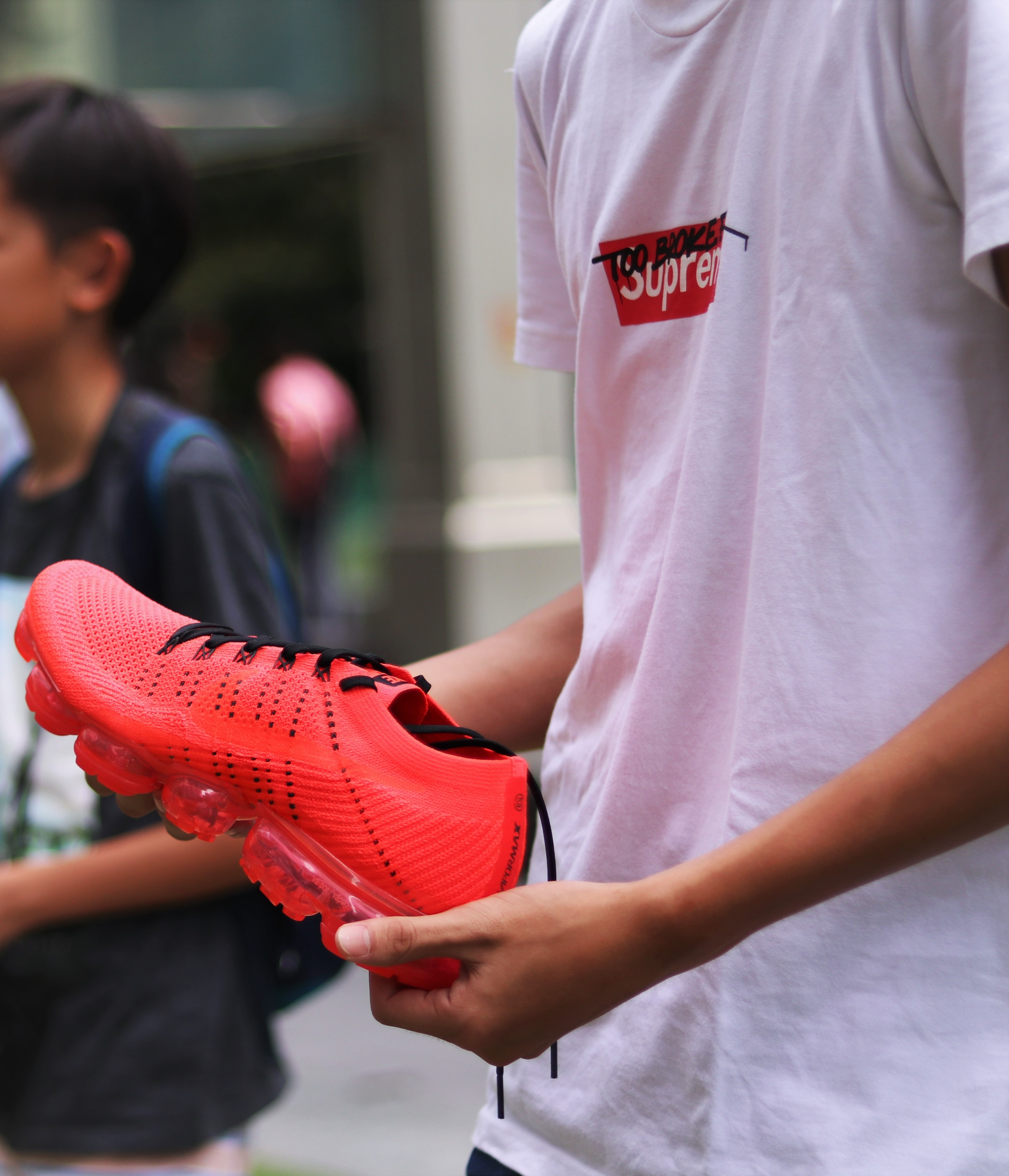 A person wearing a t-shirt that says Supreme holds a red sneaker with black laces