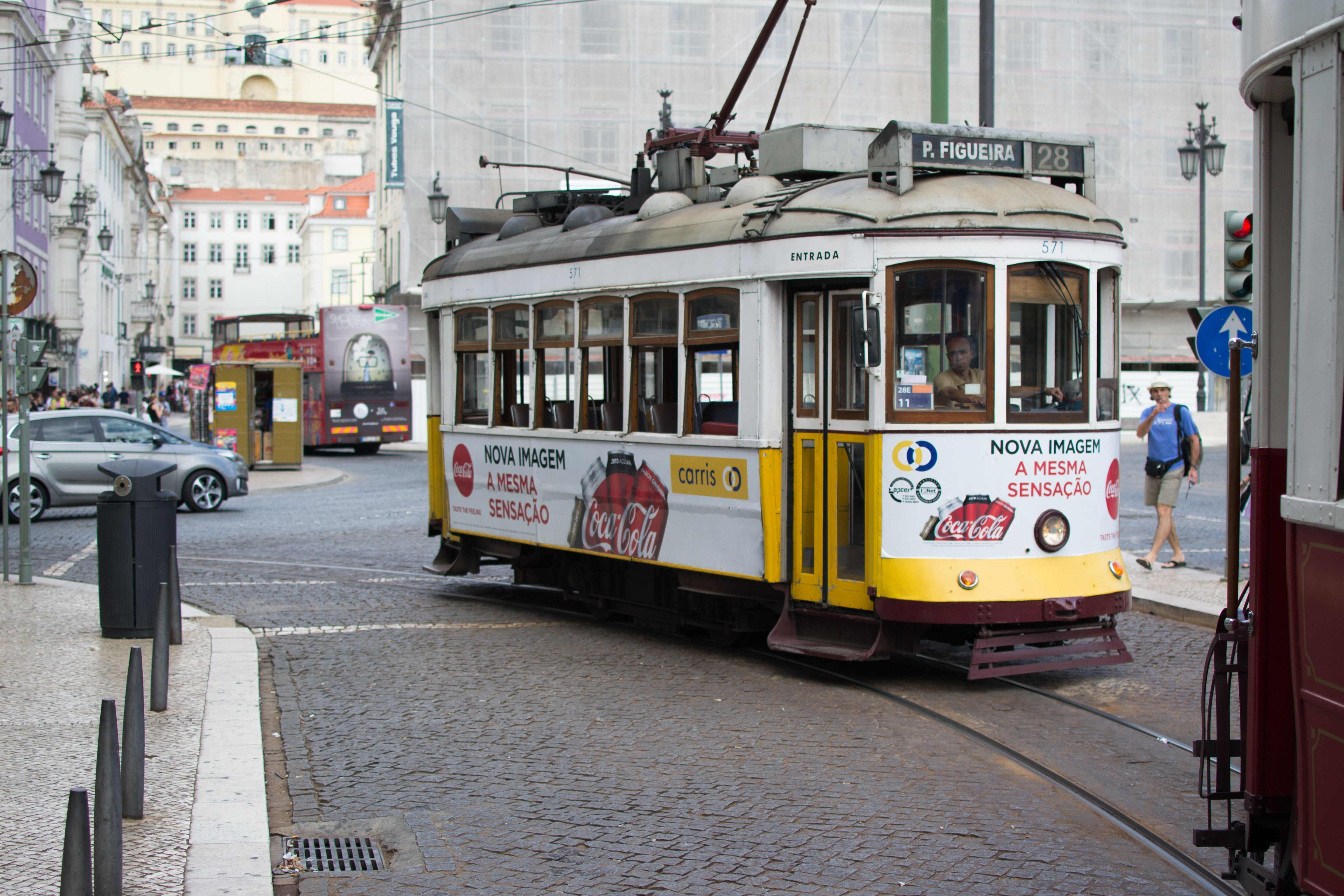 Vintage tram with ads turning in a Lisbon street