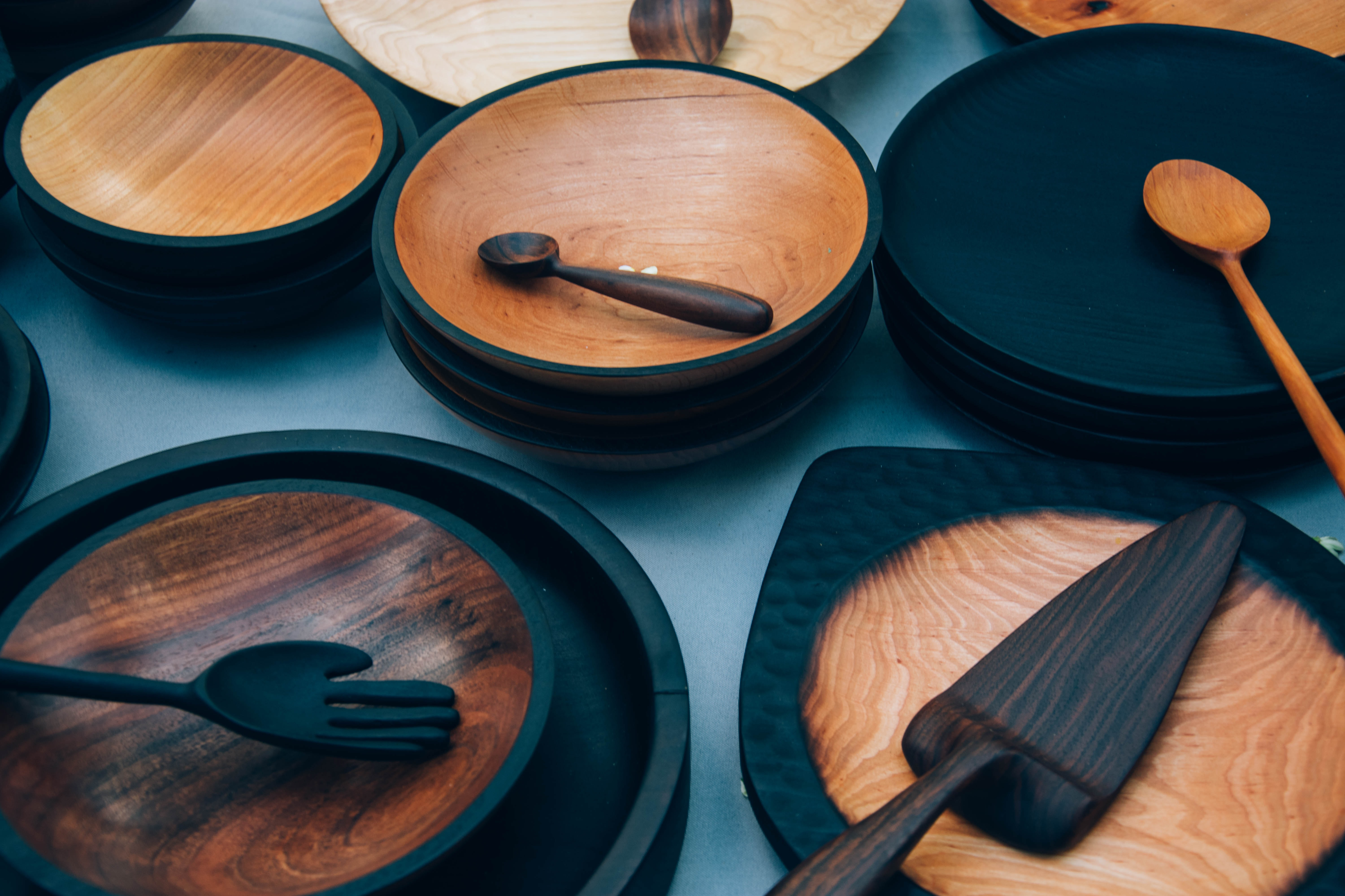 An assortment of wooden bowls, plates, and cutlery