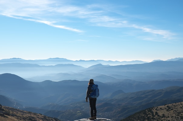 ultralight backpacker wearing backpack standing on cliff in front of mountains during daytime