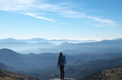 person wearing backpack standing on cliff in front of mountains during daytime hiking teams background