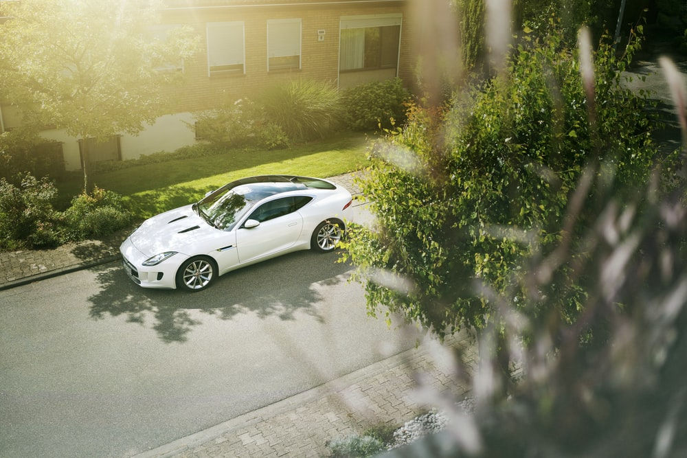 white coupe parked near house