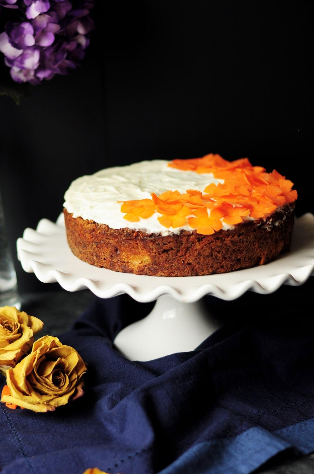 white and orange icing-coated cake on scalloped edge white ceramic cake stand