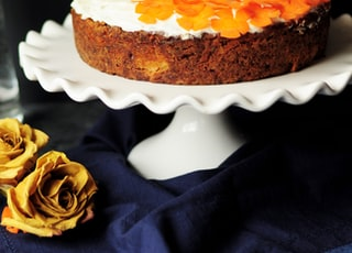 white and orange icing-coated cake on scalloped edge white ceramic cake stand