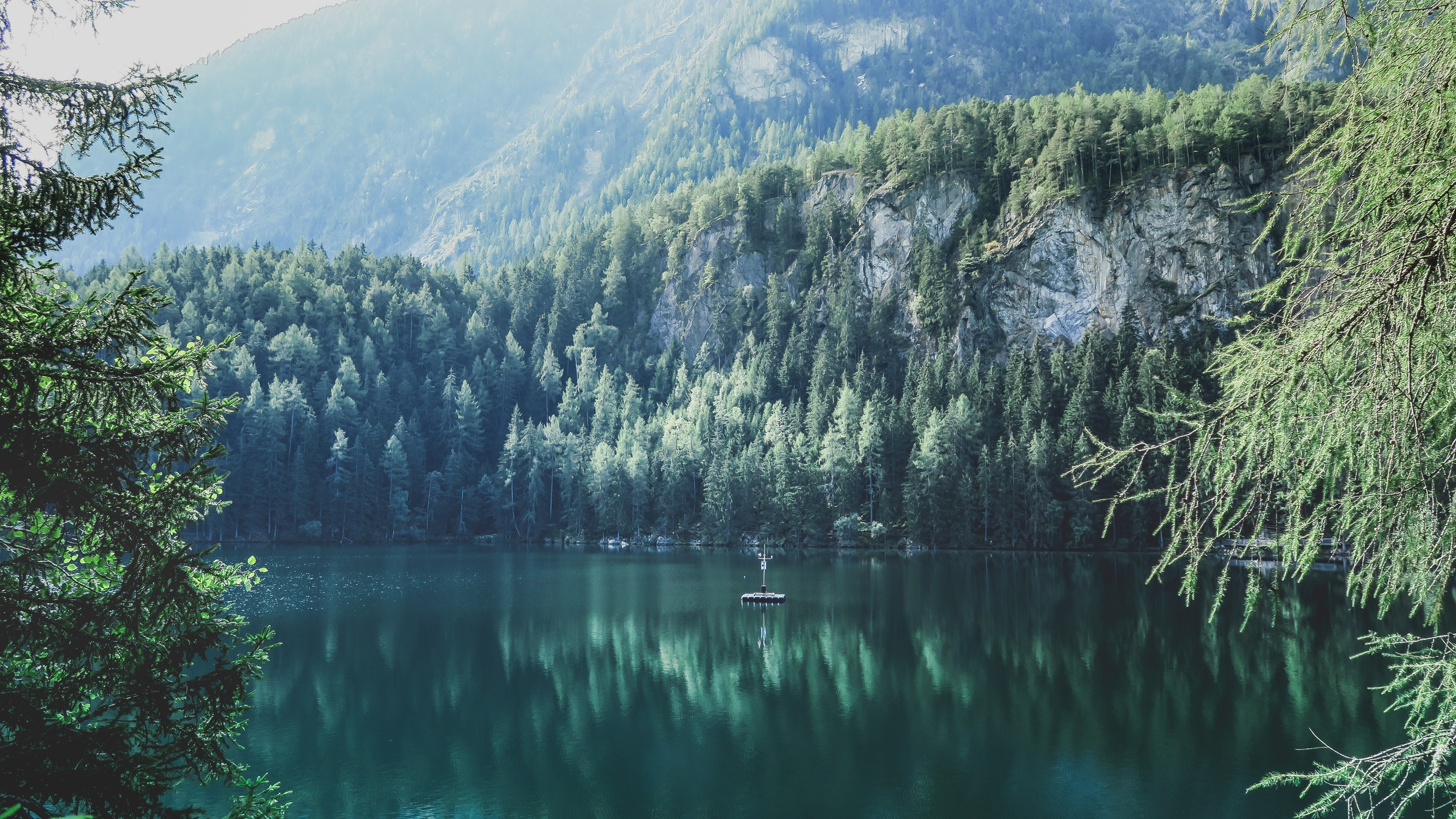 Rocky slopes and woods overlooking the still surface of Lake Piburger See