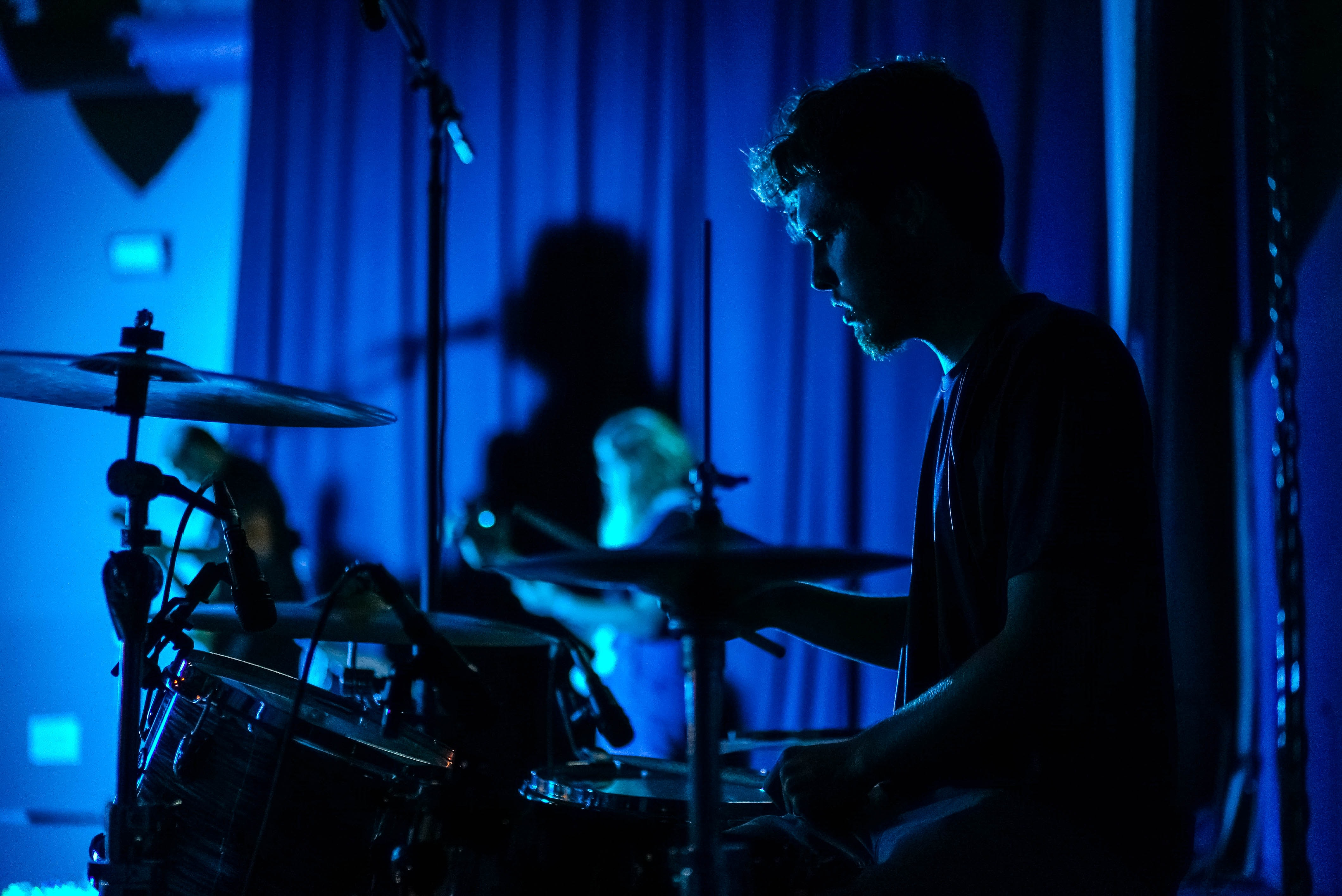 A man with a beard playing the drums in a room lit with a blue light