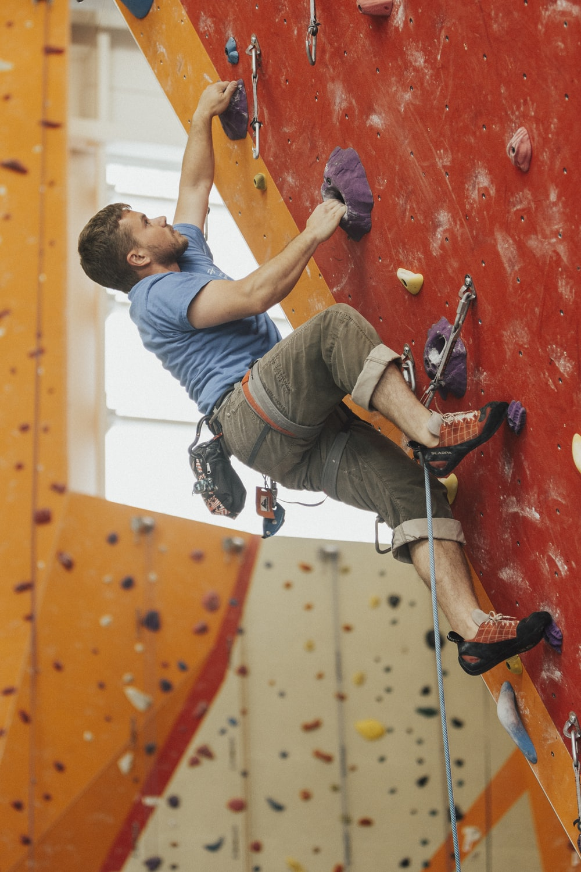 man wall climbing on red wall