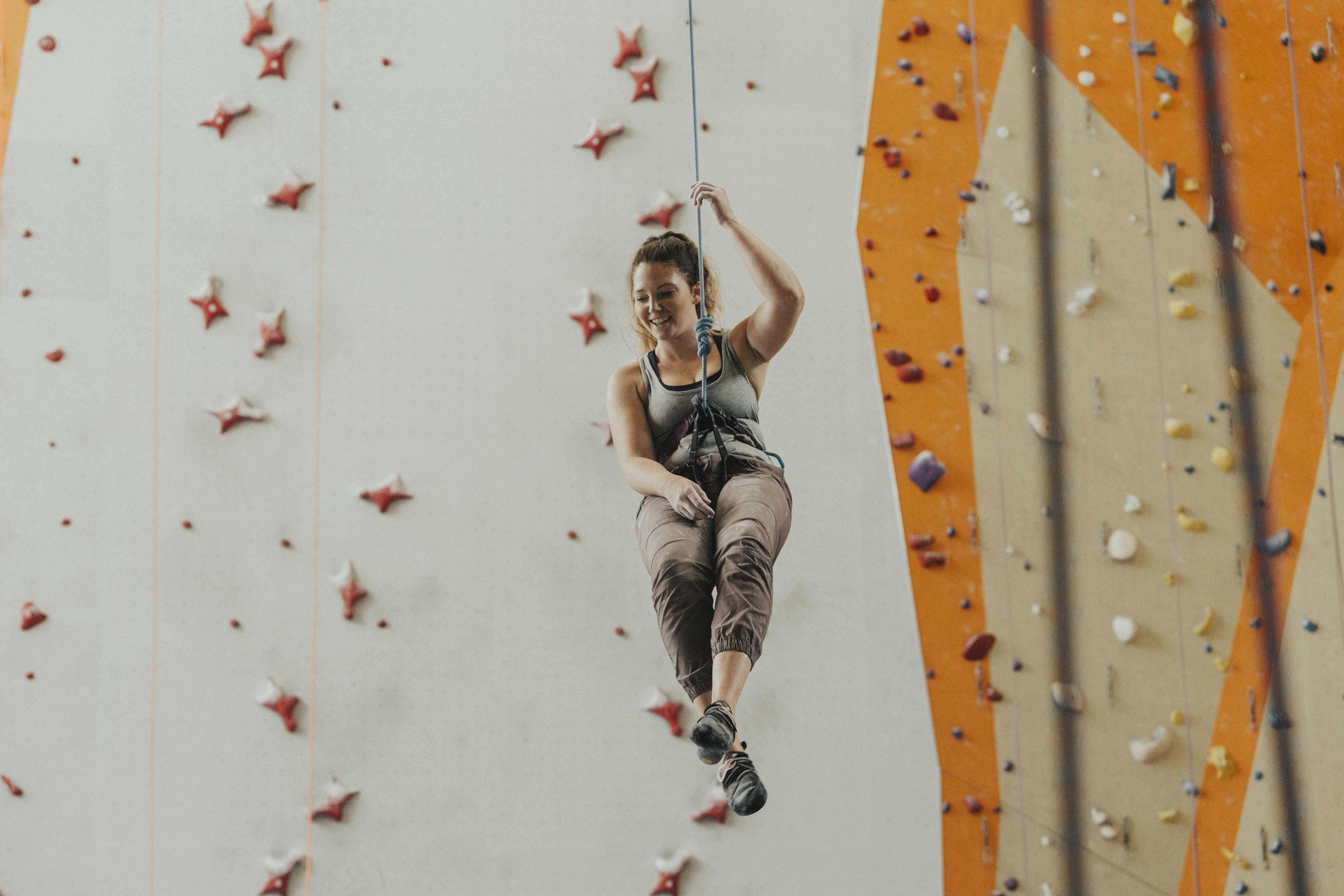 A woman suspended on a rope in front of a climbing wall at Stone Summit Kennesaw