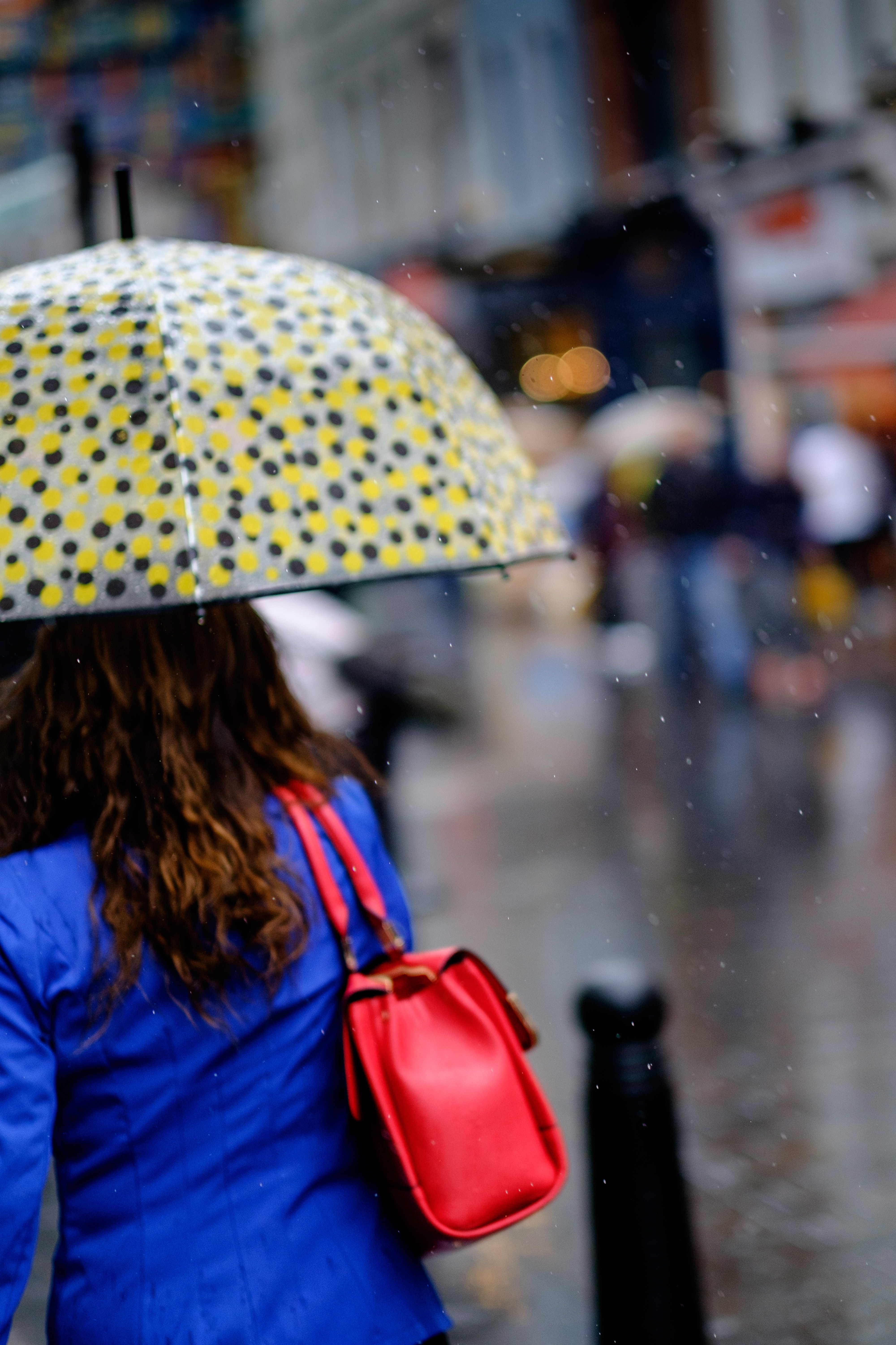 A woman holds a polka-dotted umbrella in rainy London Chinatown