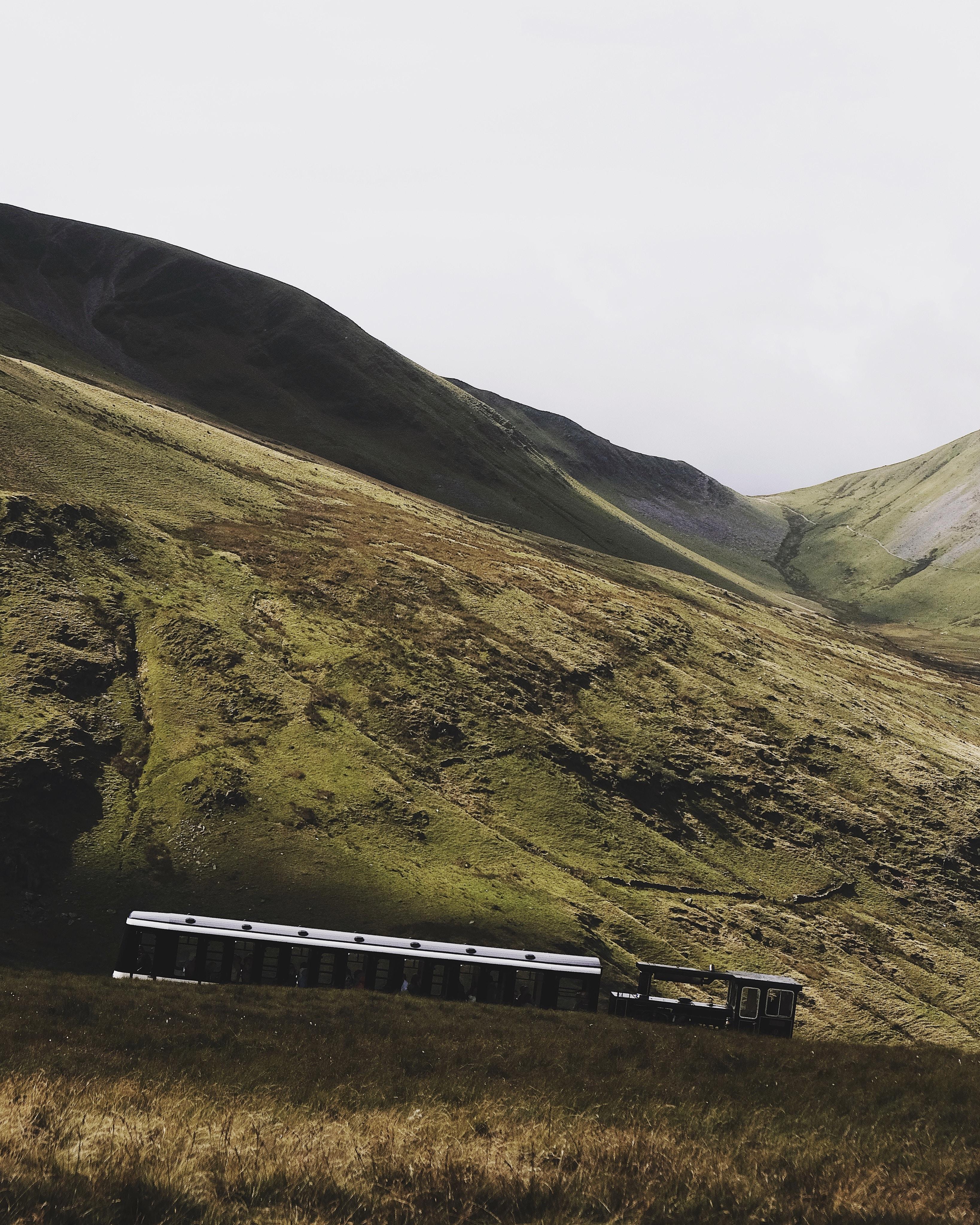 train beside mountain under gray sky