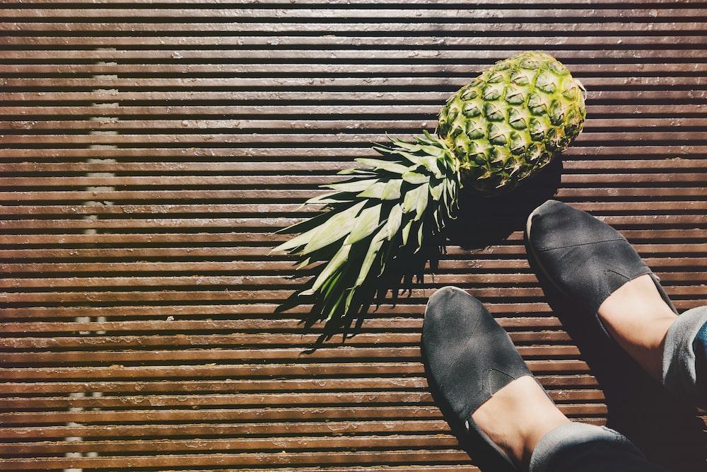 pineapple beside person's feet