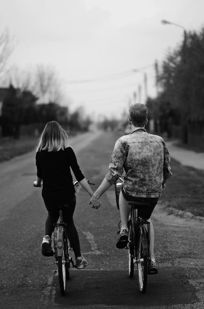 A guy and girl holding hands while cycling together on separate bikes on an empty road