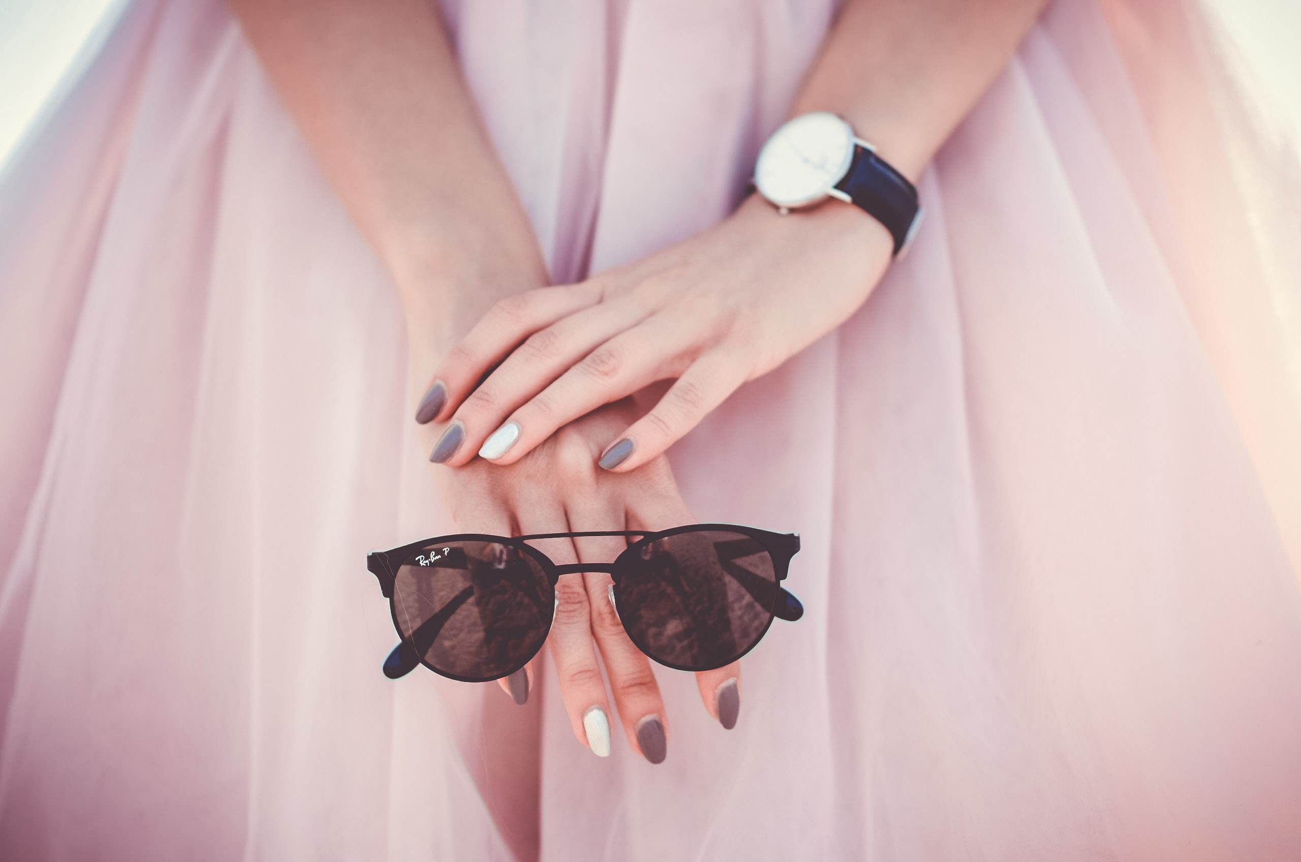 A close-up of a woman's hands with colored nails holding a pair of sunglasses.