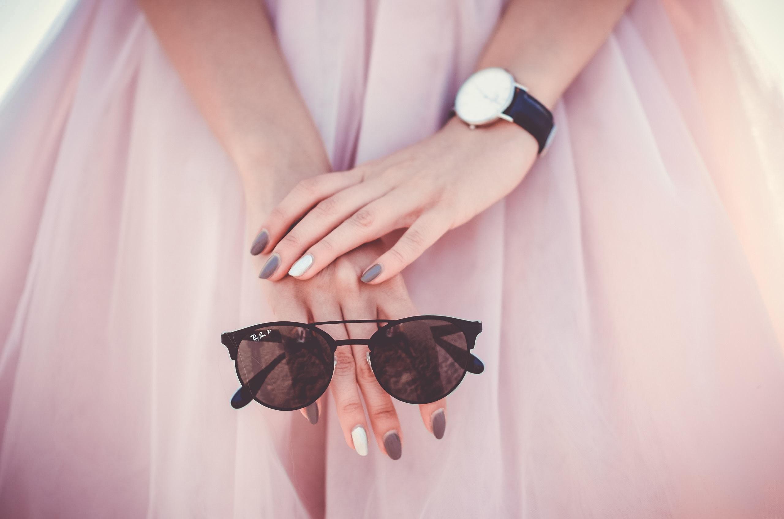 woman holding black Ray-Ban sunglasses
