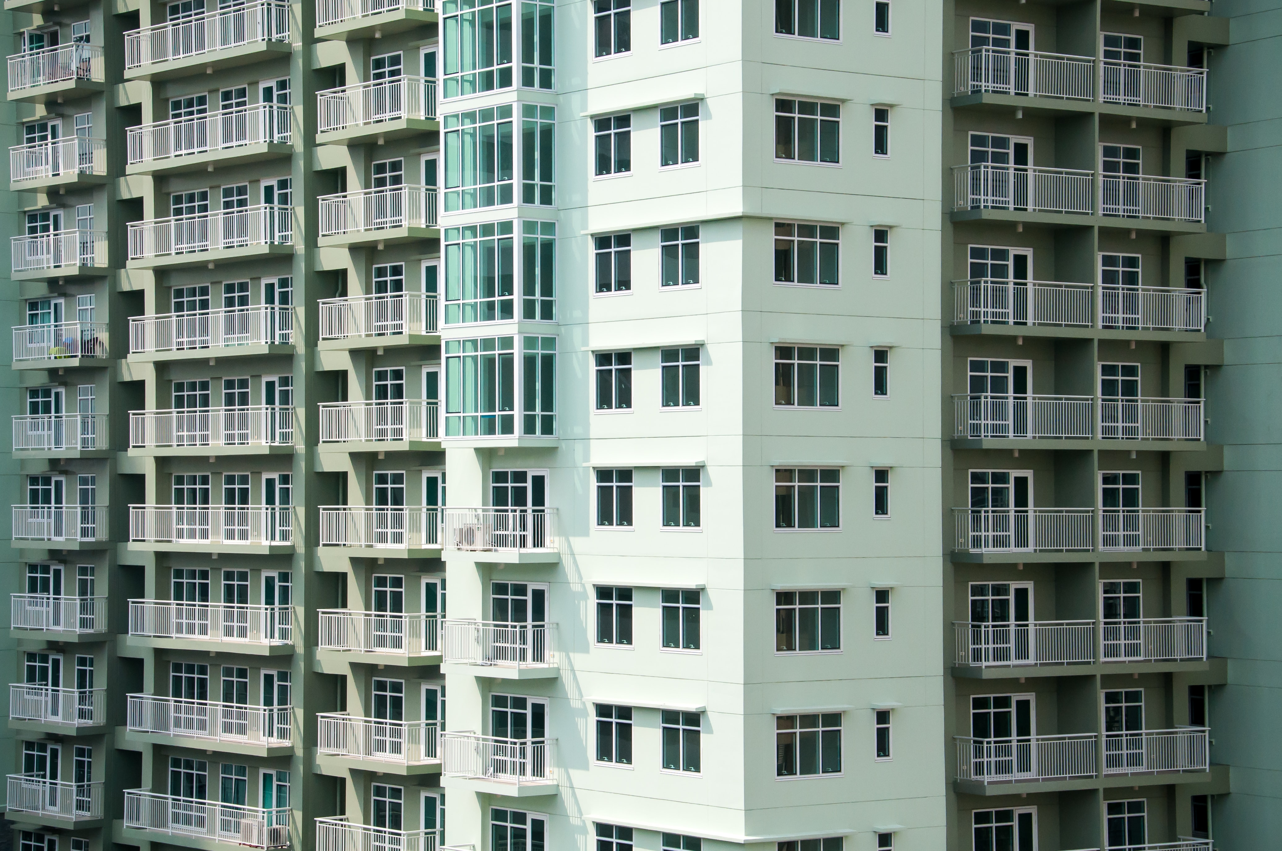 Multi-colored apartment building with white balconies and windows