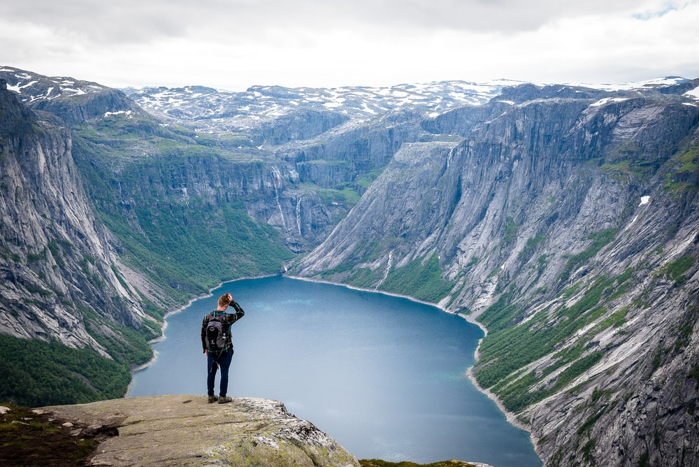 man in black jacket with black backpack standing on top of cliff above a lake at daytime
