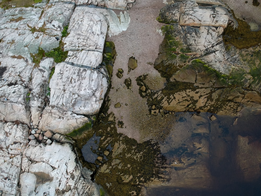 aerial photography of rock formations near body of water
