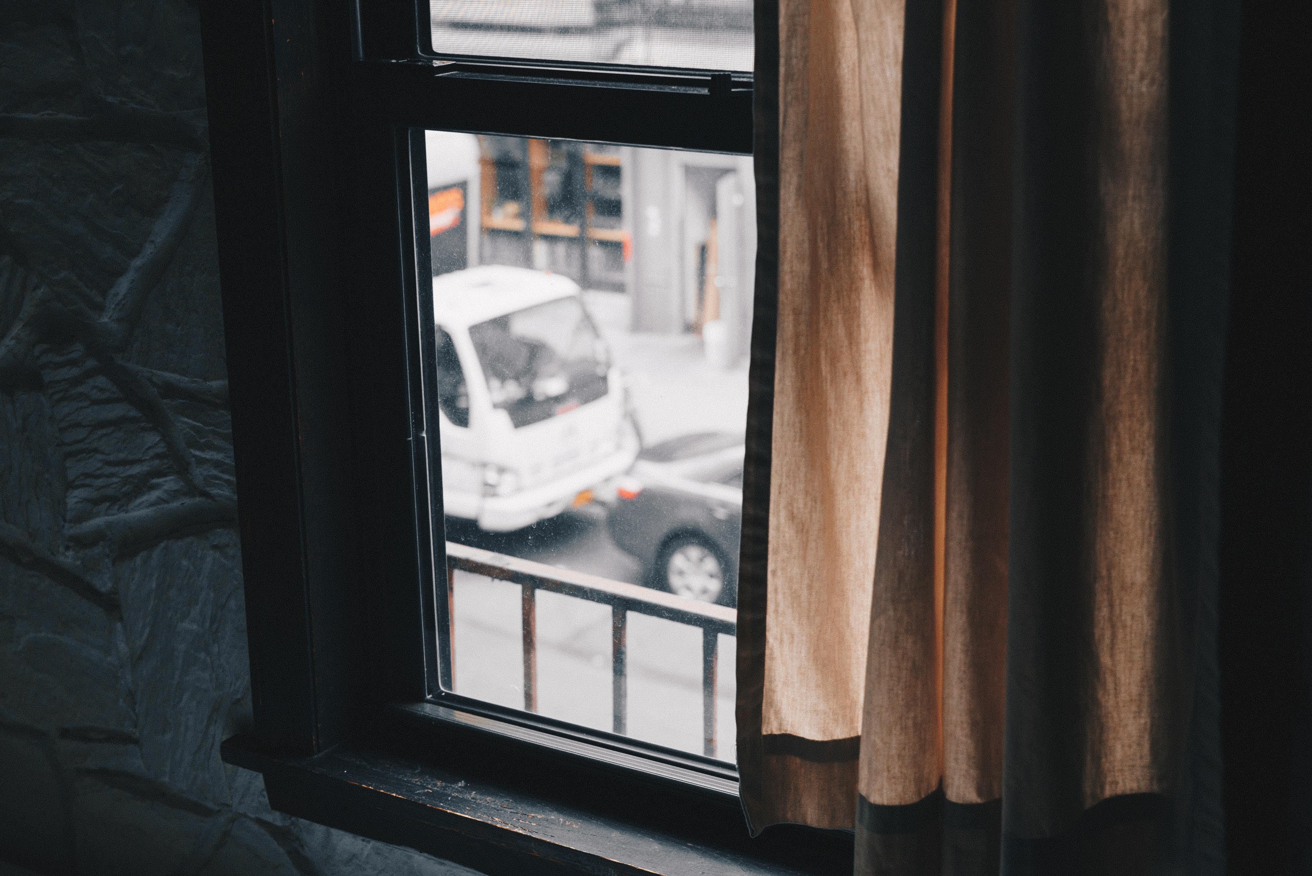 black sash window near brown curtain