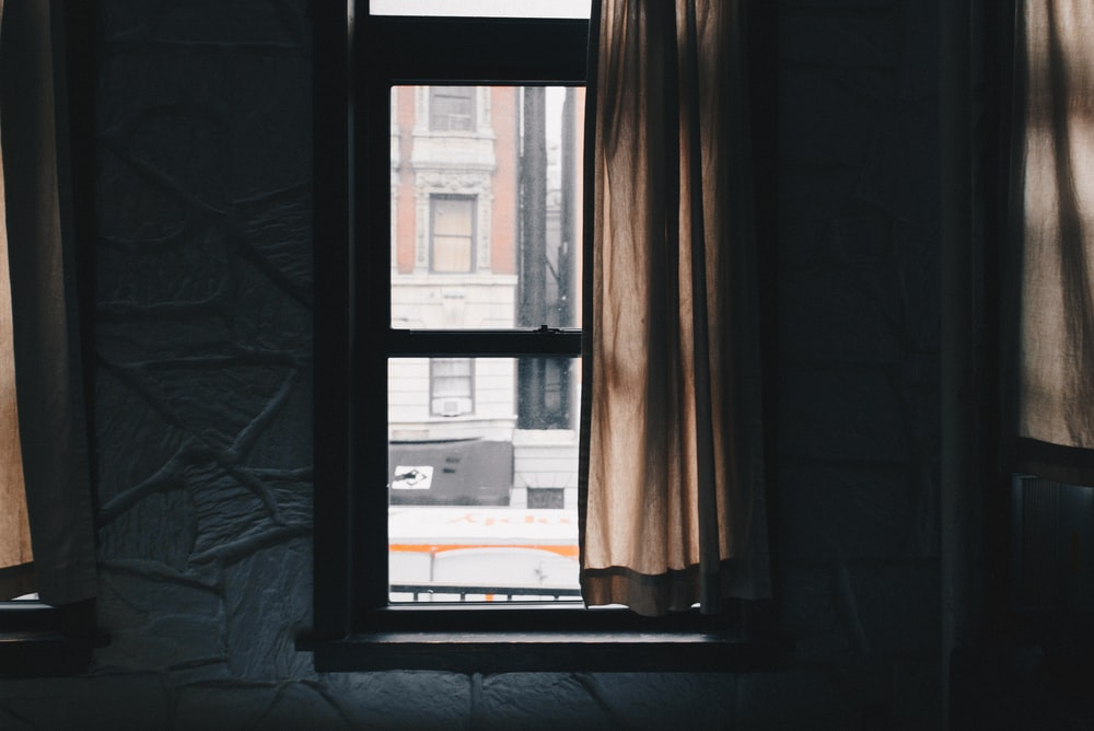 brown window curtain beside black wooden sash window