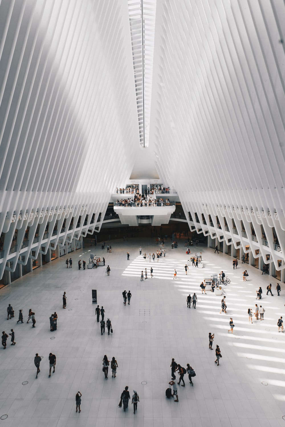 people walking inside white concrete building