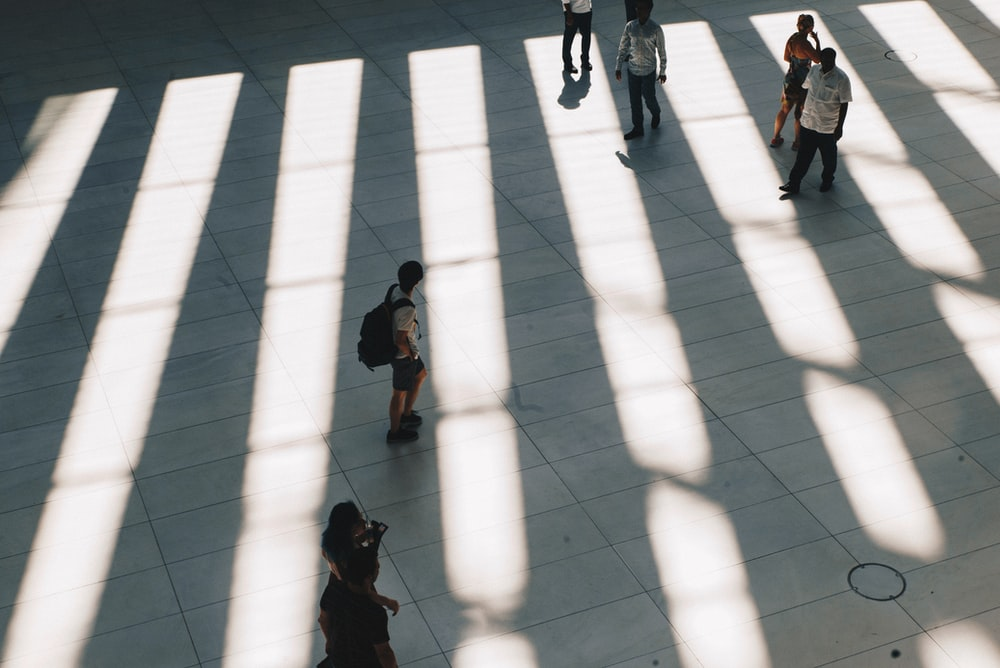 aerial photo of people walking on gray concrete pathway during daytime