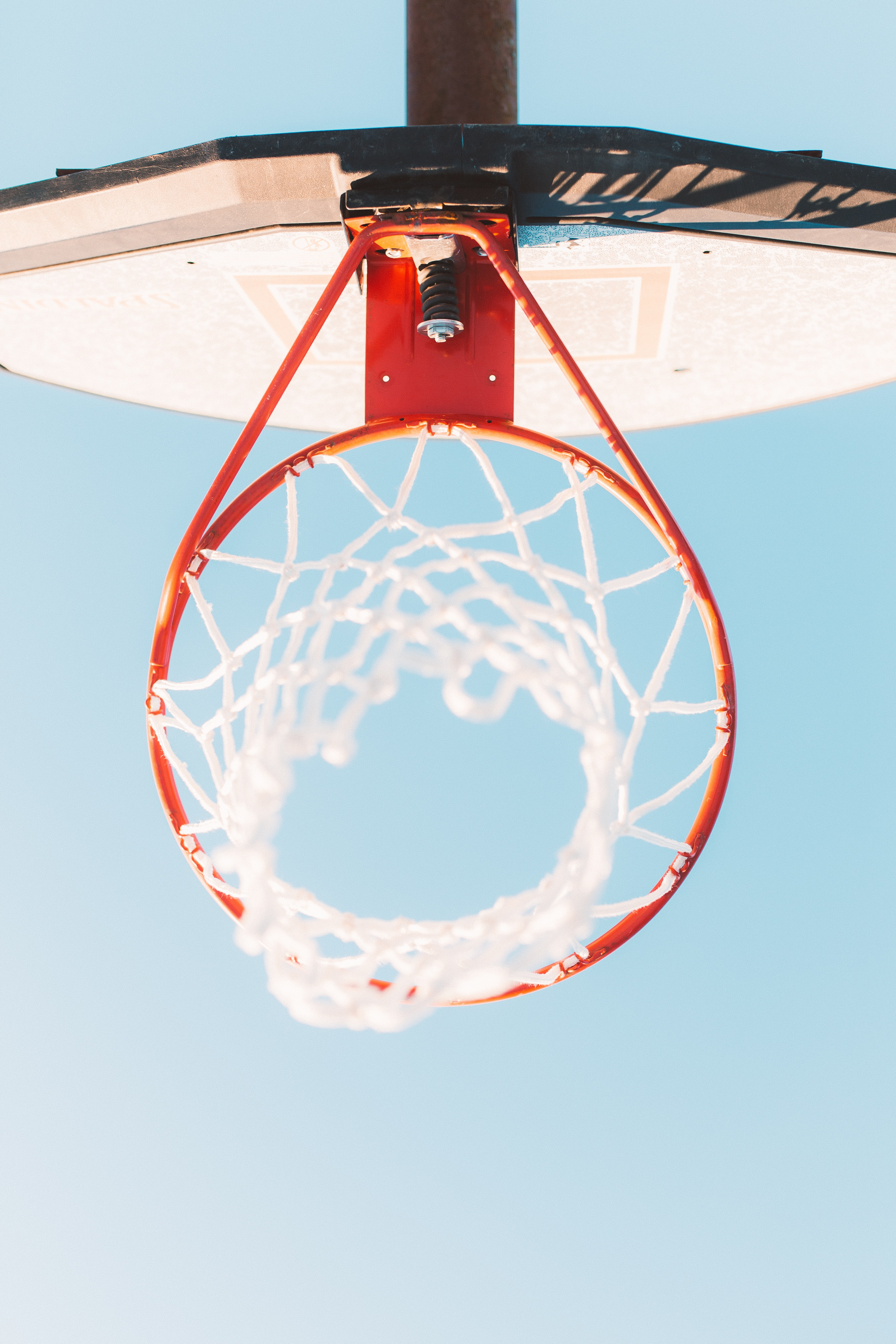 Photo taken under an outdoor basketball hoop