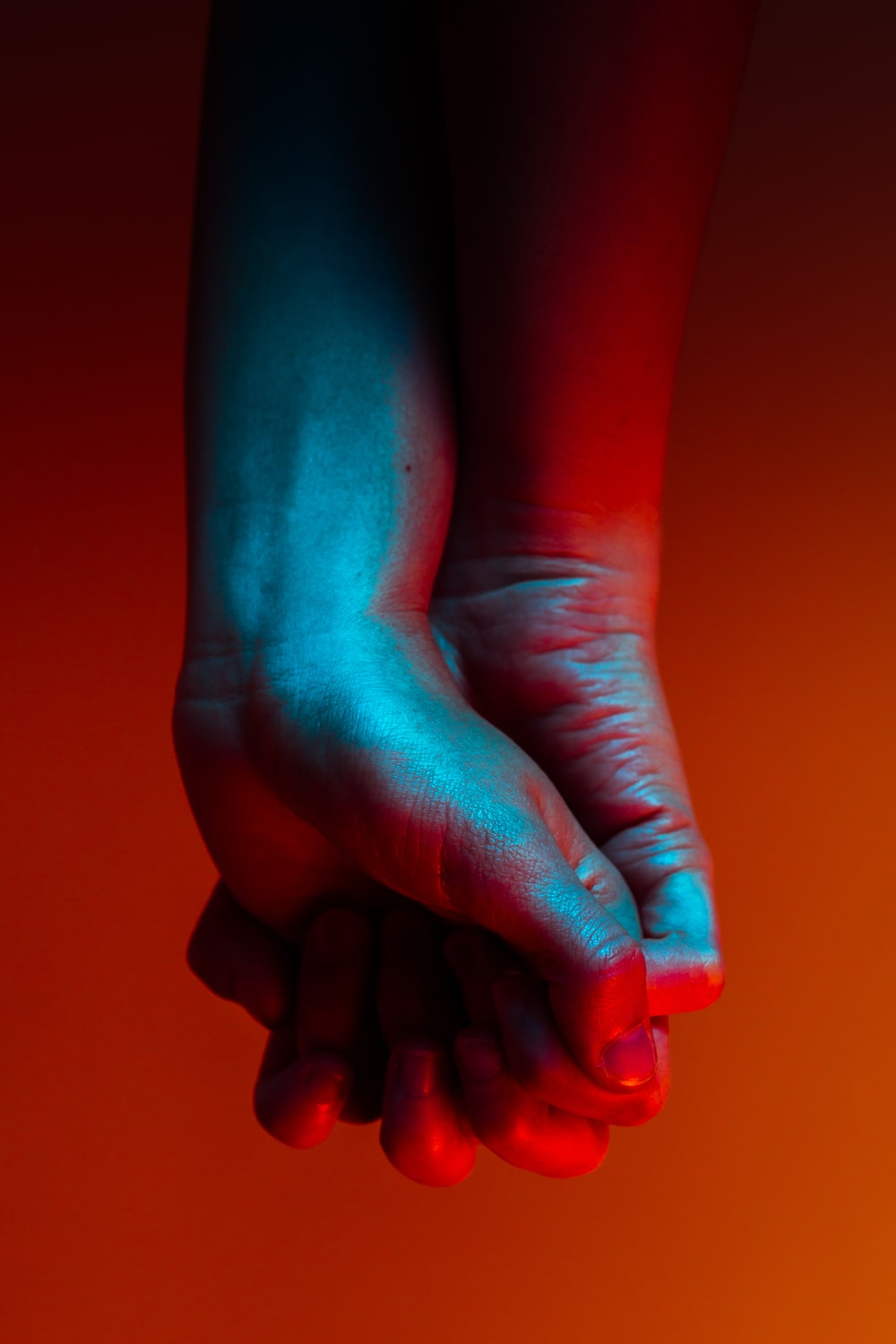 two person holding hands near orange background