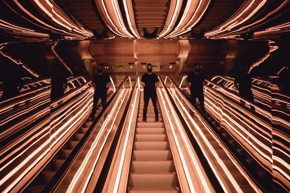person on mirrored escalator