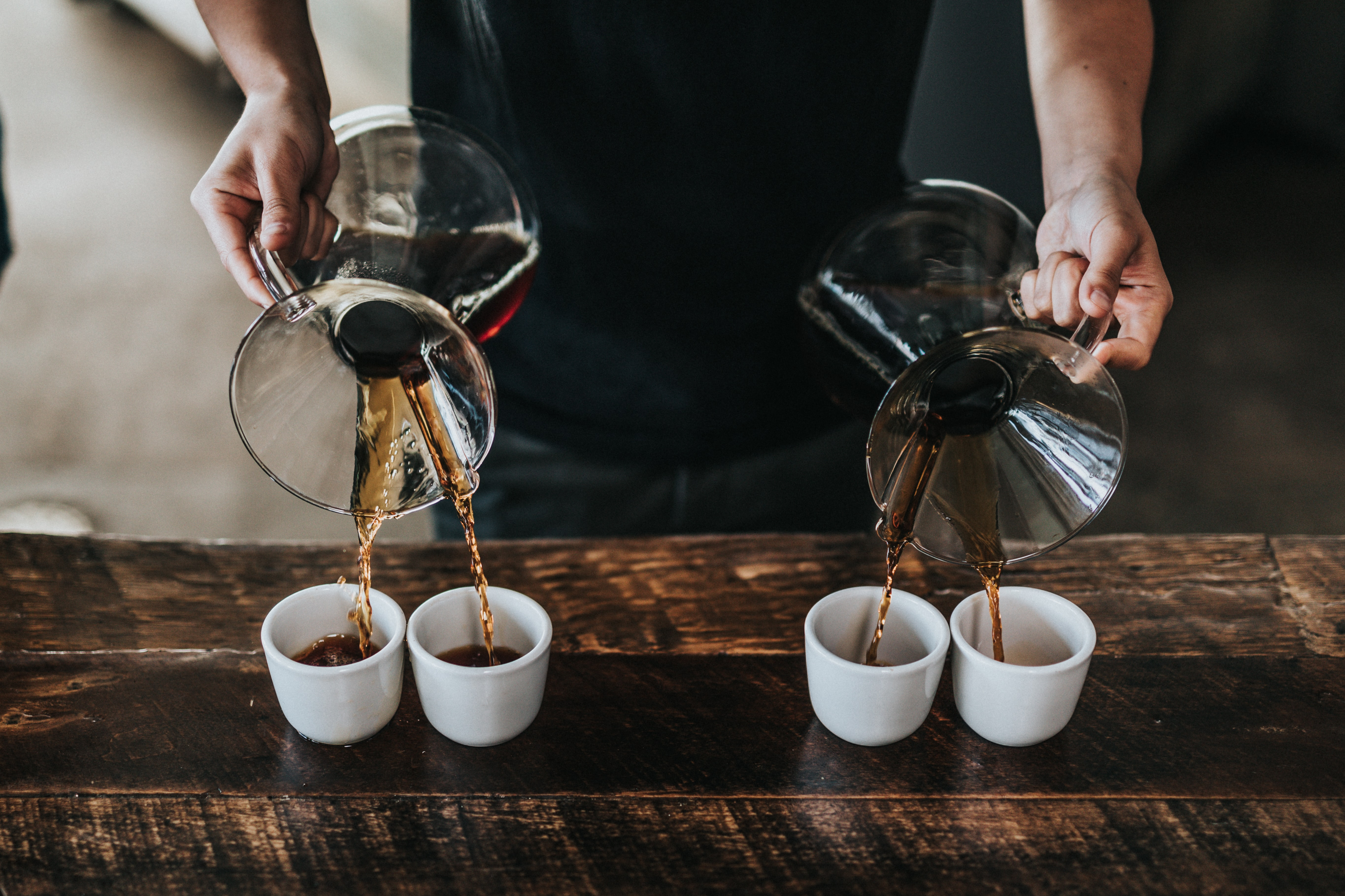 A barista pouring coffee to four cups at once