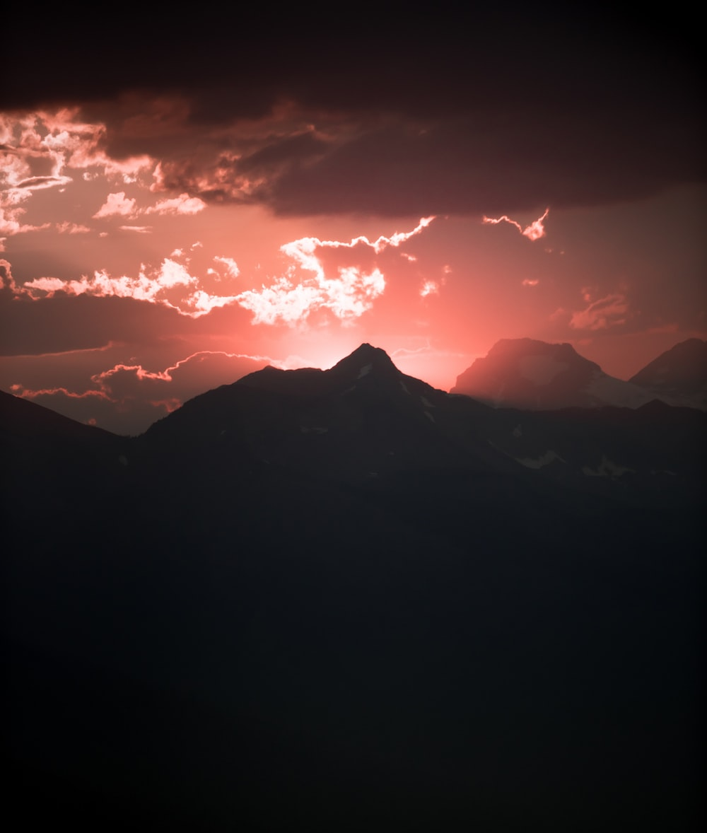 silhouette of mountain under red sky panoramic photography