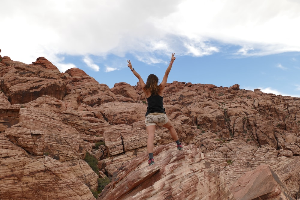 person in black tank top standing on mountain during daytime