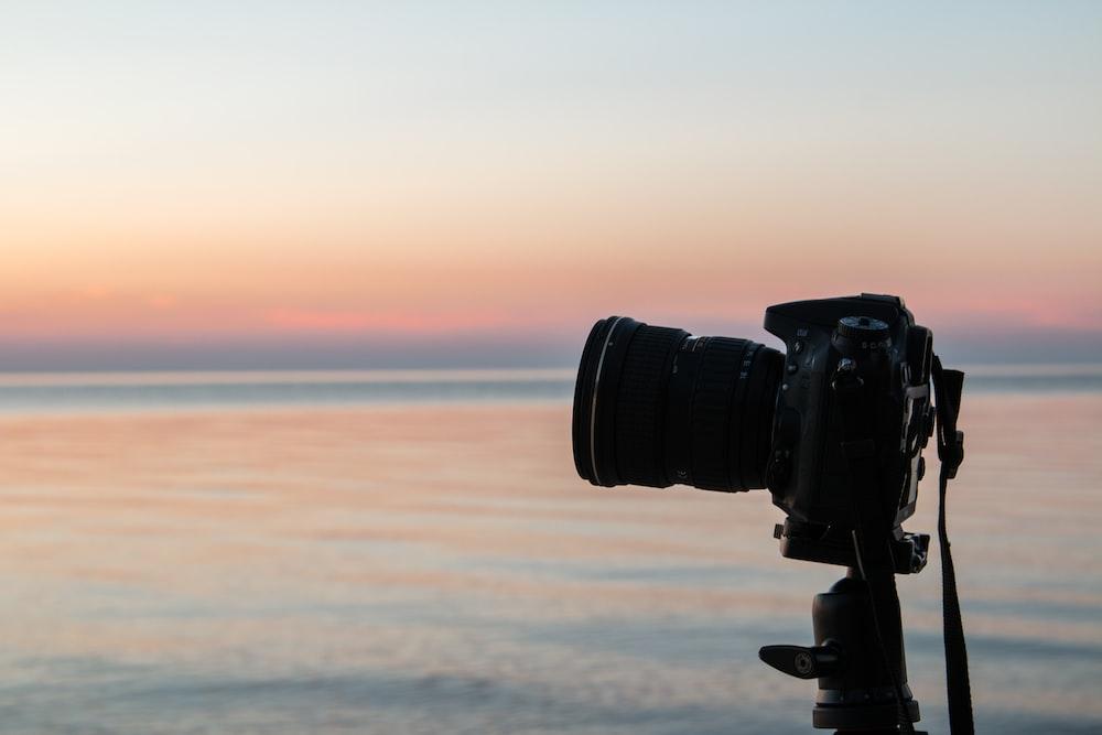 photo black DSLR camera on tripod
