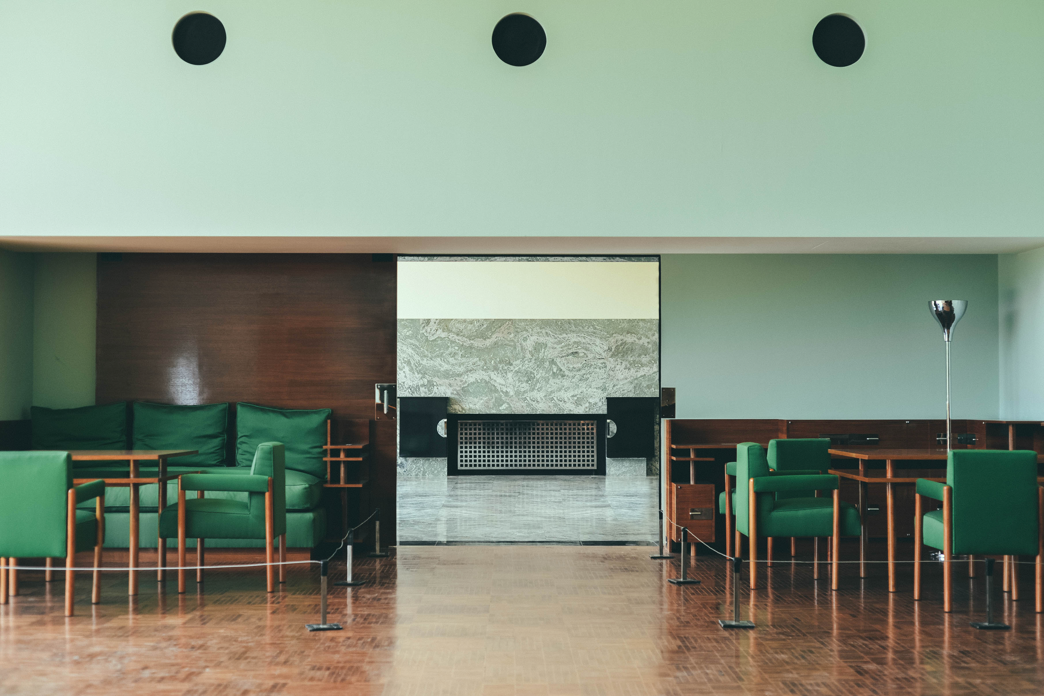 Inside the hall of the Villa Cavrois with green sofas and contemporary wall panel.