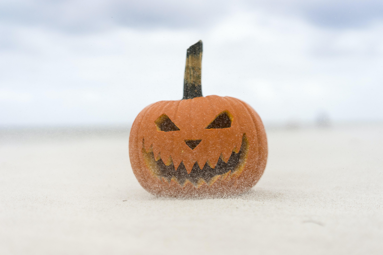 jack-'o-lantern on sand at daytime