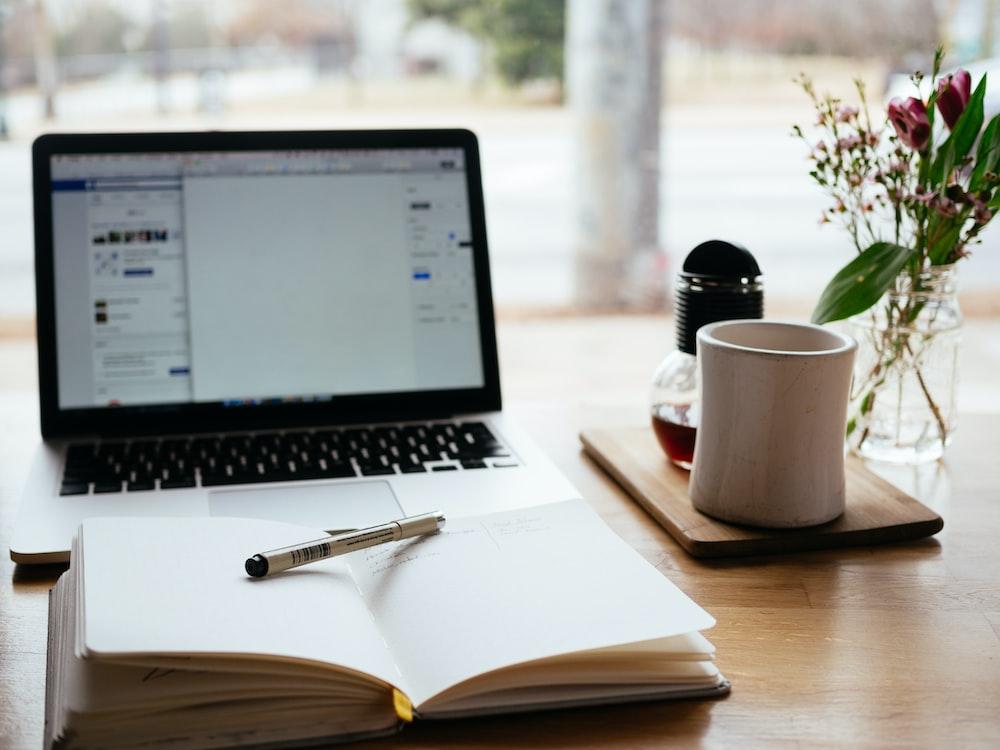 MacBook Pro near white open book