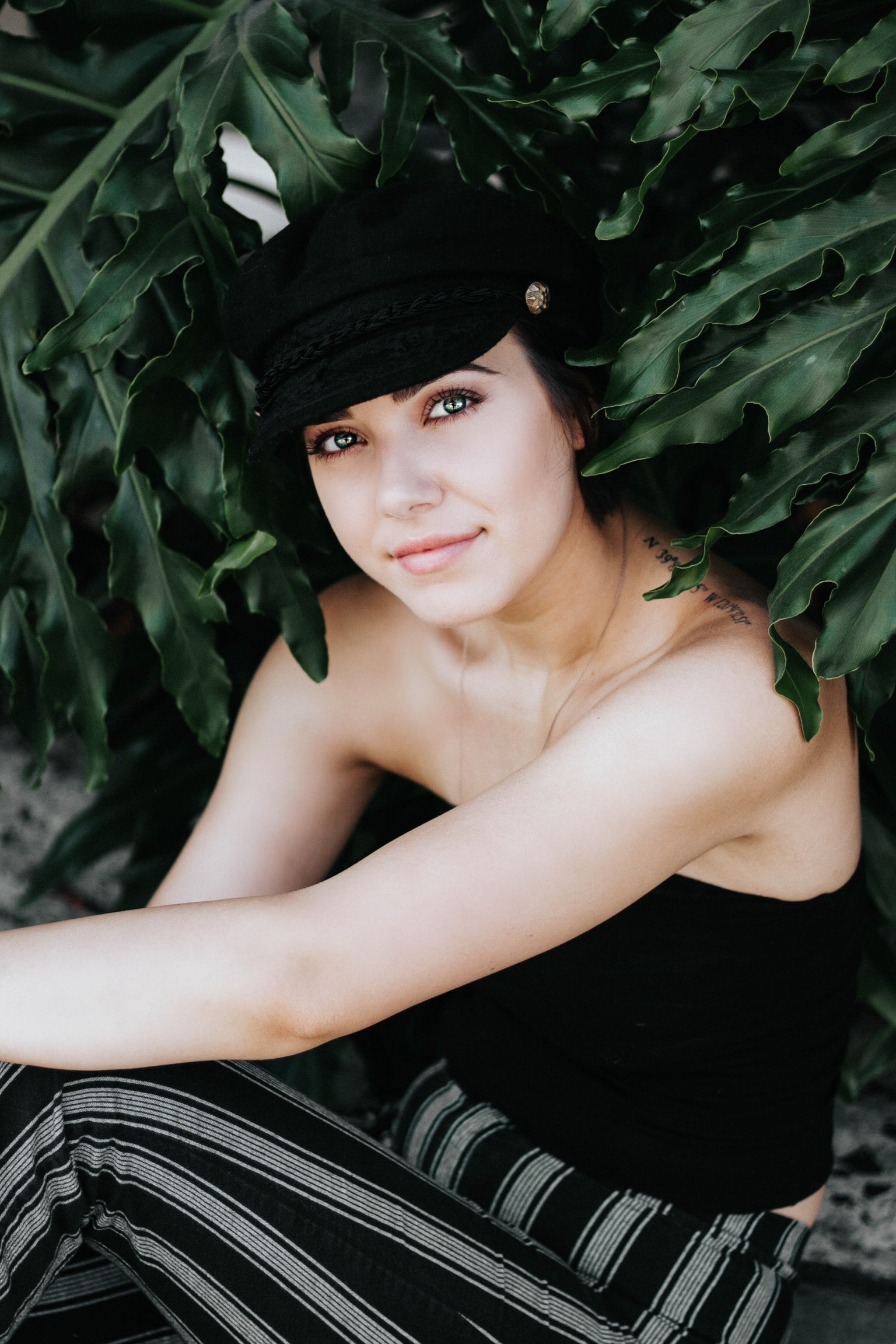 smiling woman in black strapless top and black and white striped pants