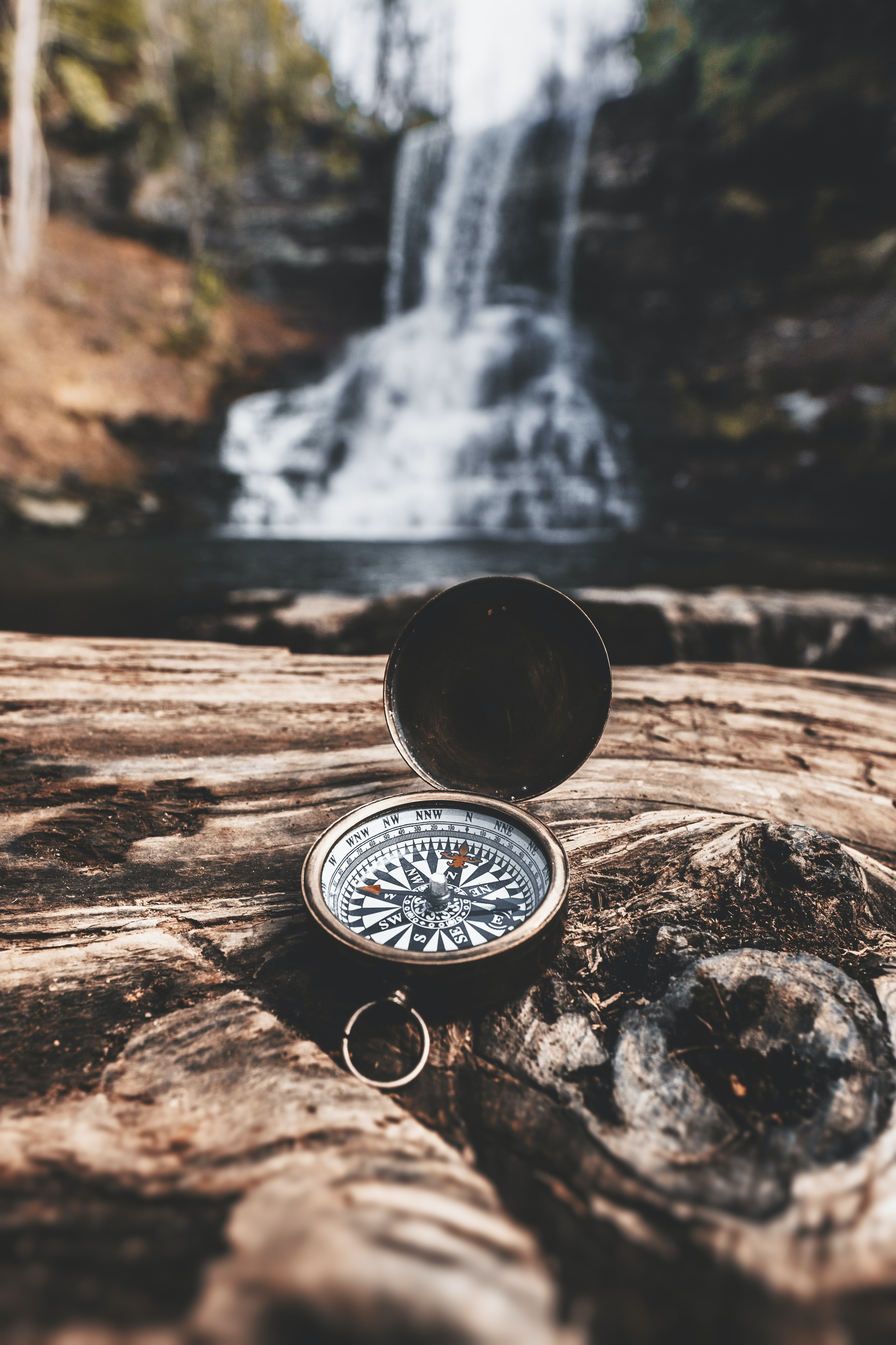 brass-colored compass on brown wooden tree stump in front of waterfalls during daytime