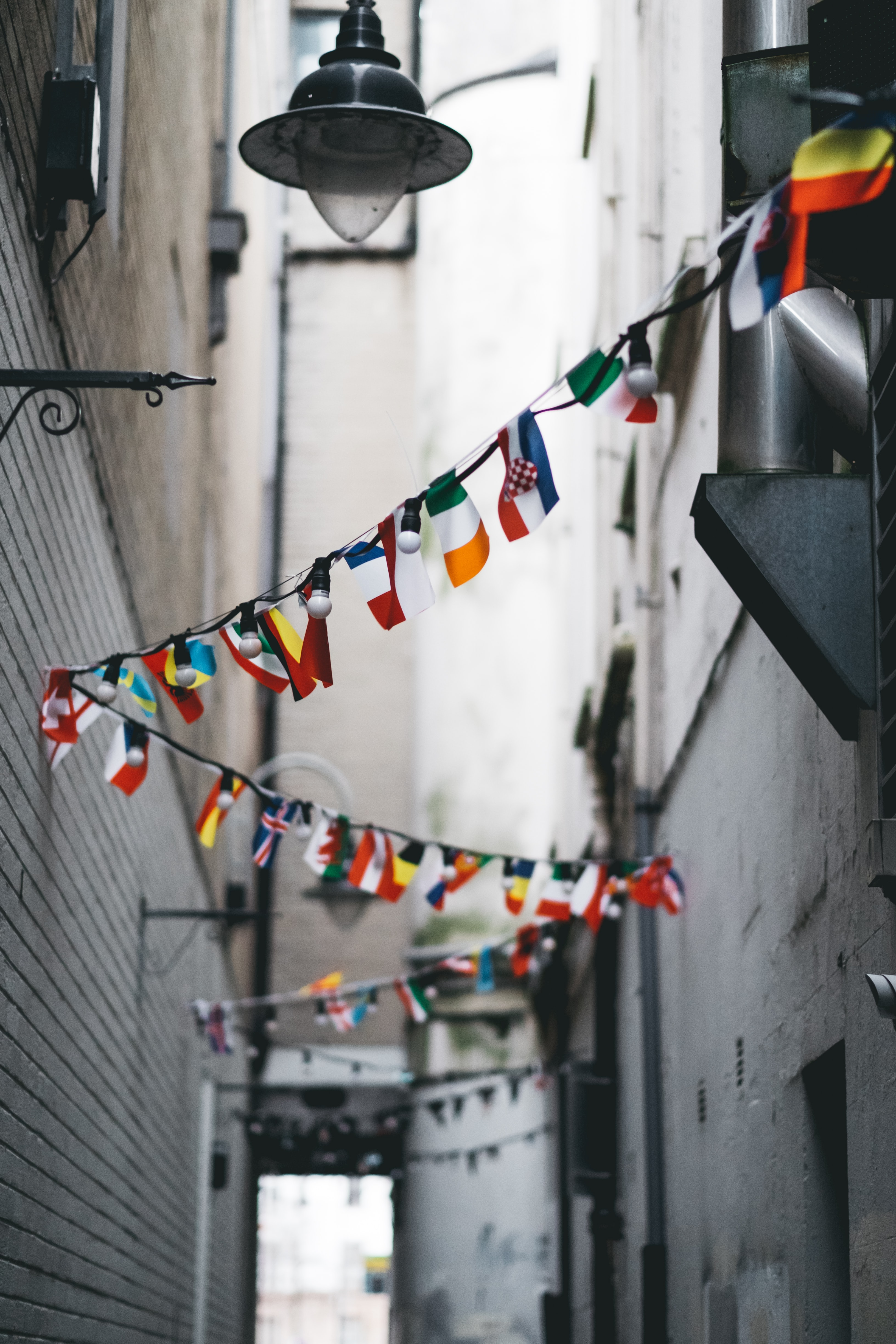 a line of flags is intertwined with a string of light in the alleyway.