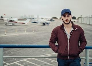 shallow focus photo of man maroon full-zip jacket