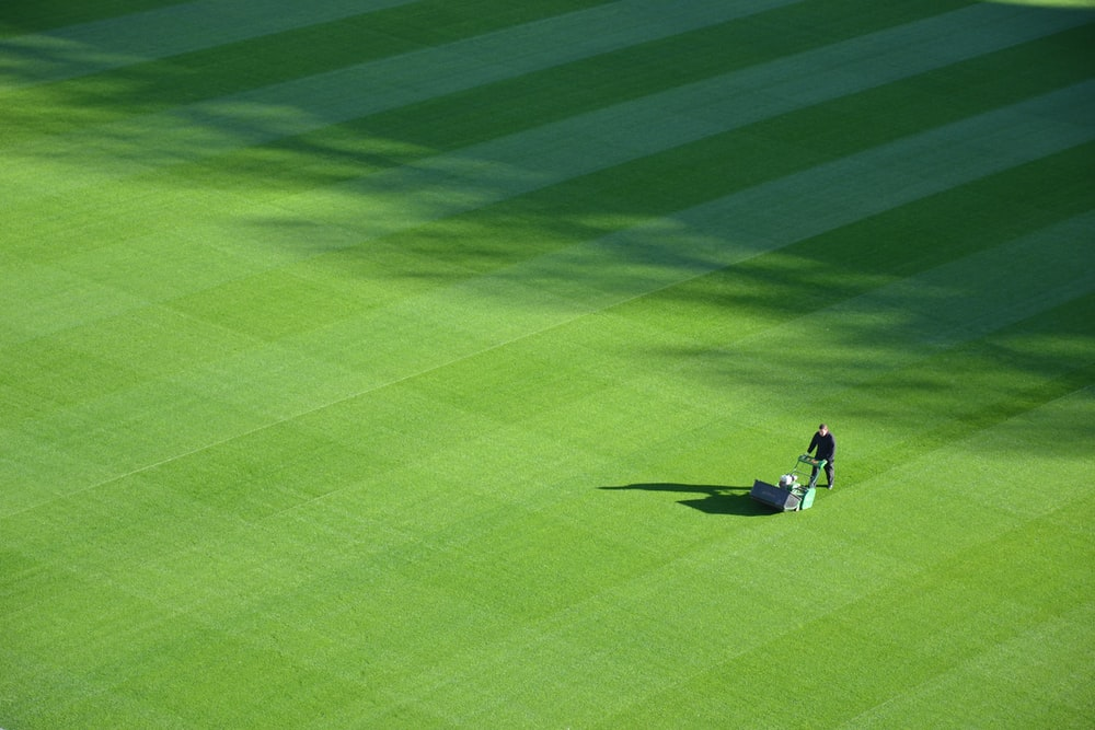 aerial photography of person trimming sports field during day