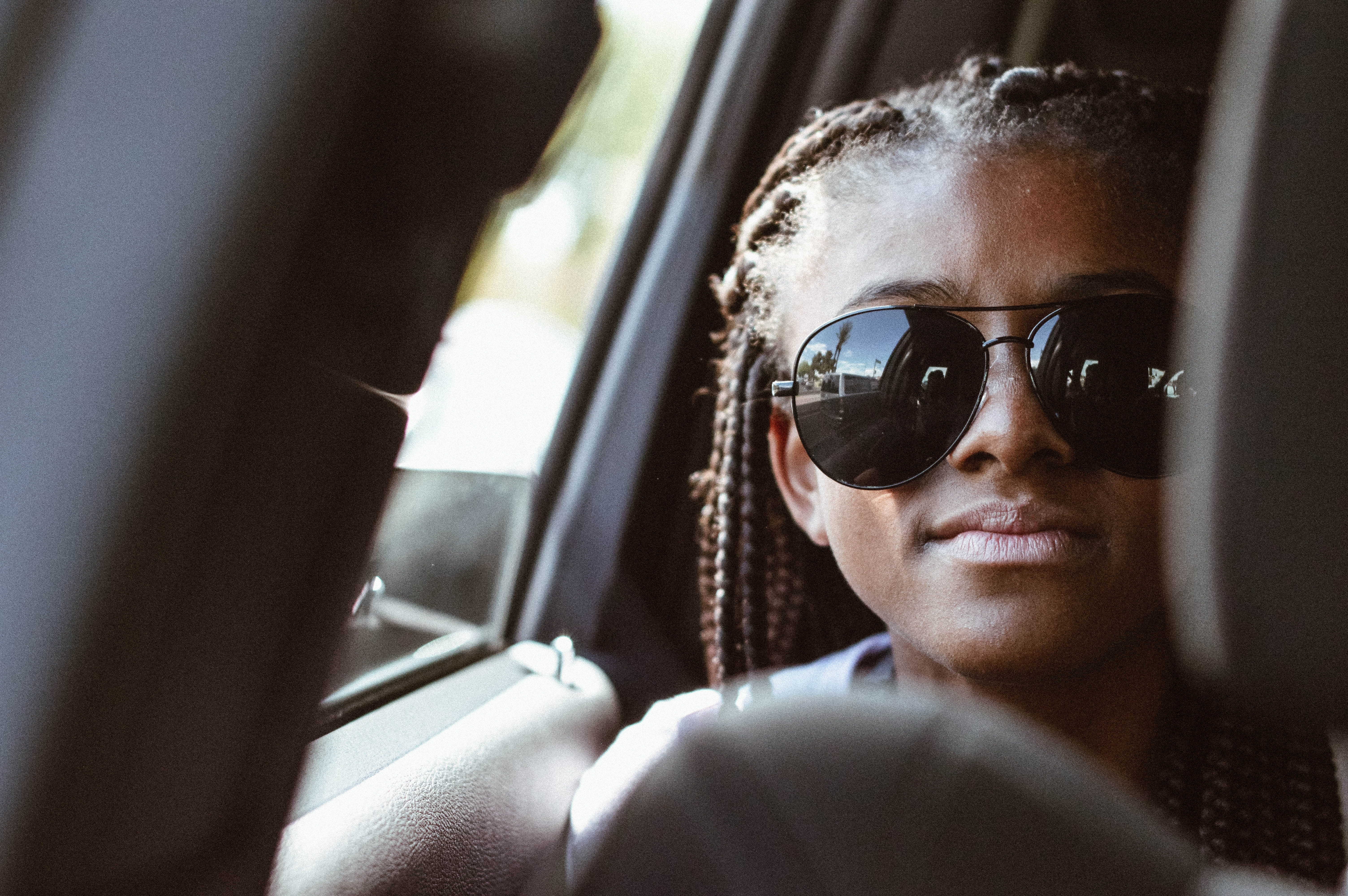 A woman in braids and sunglasses riding in a car, pictured through the seats