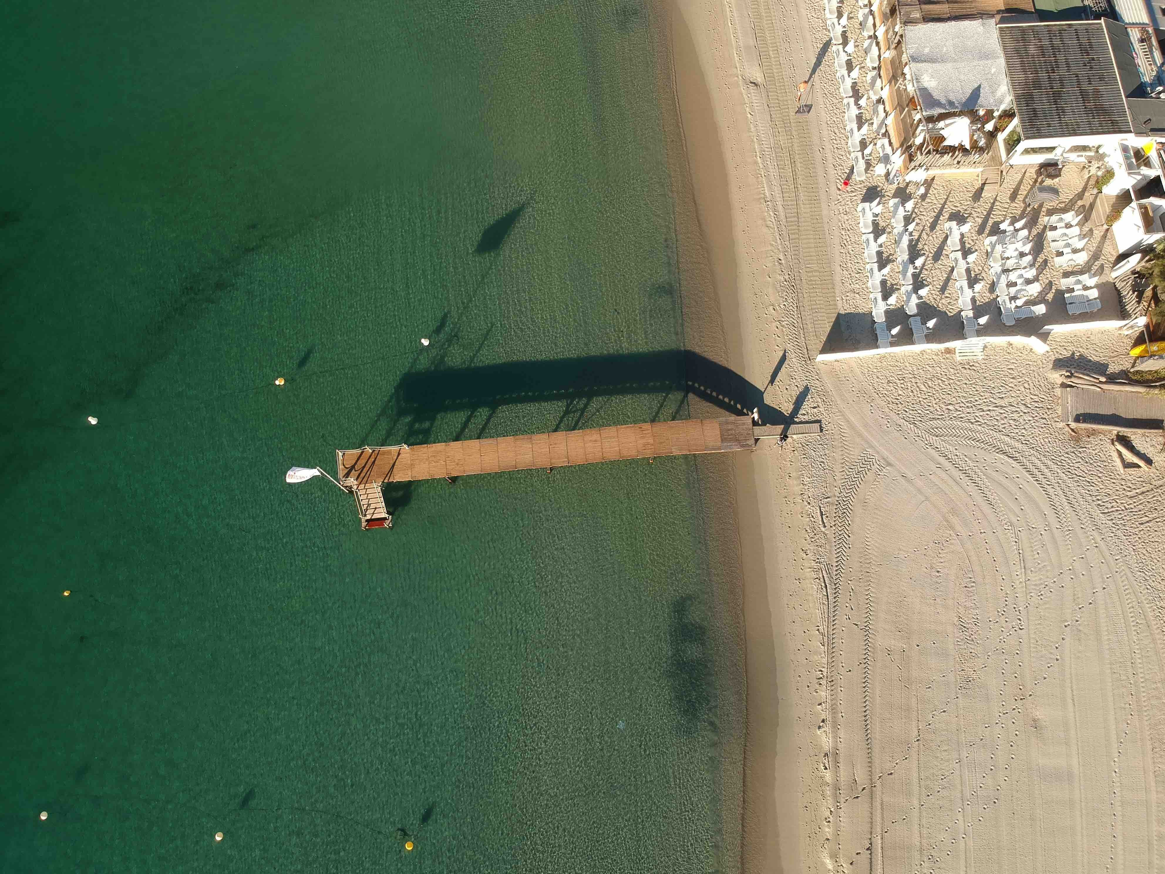 aerial photo of seashore and brown wooden dock towards sea during daytime