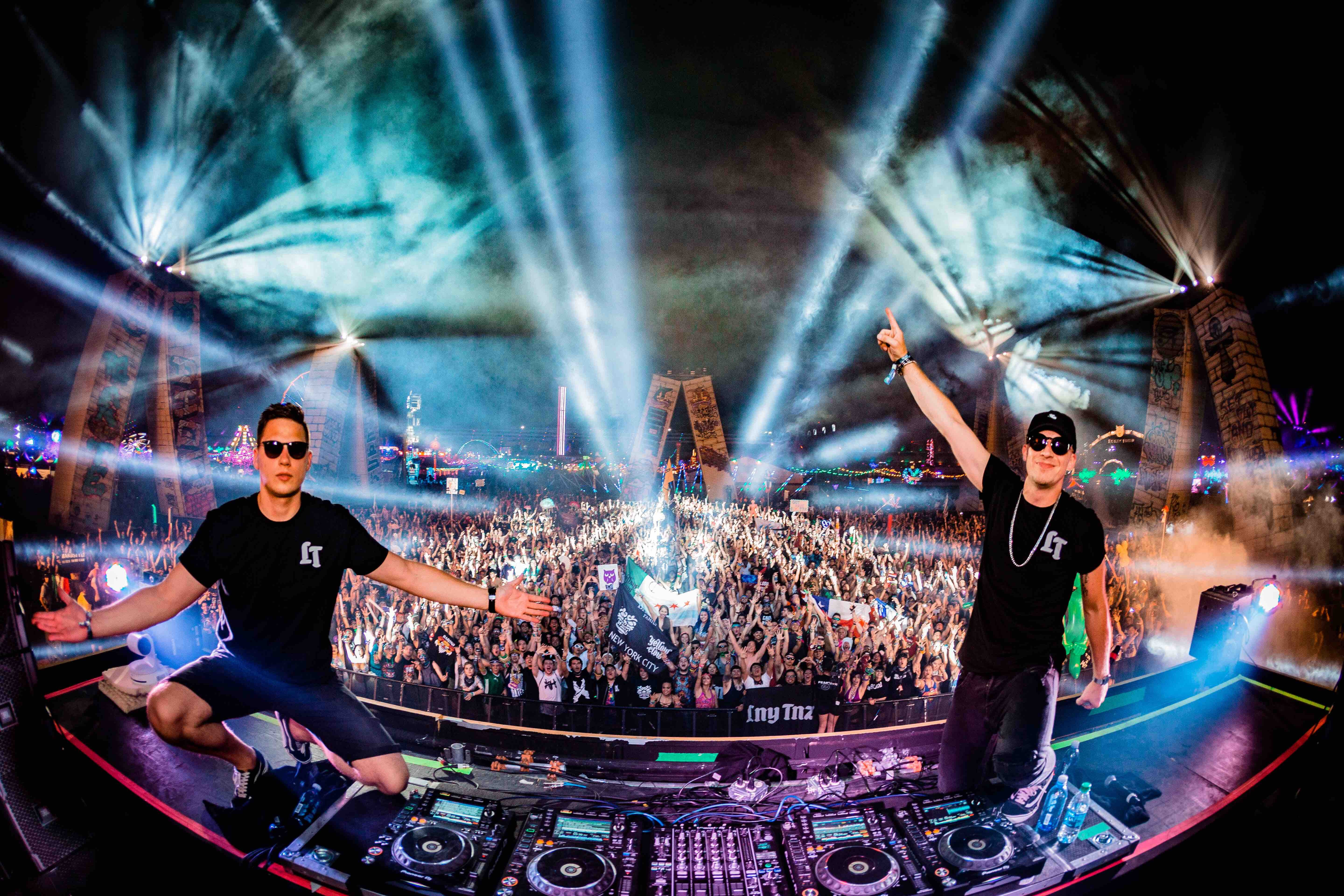 DJs looking at the camera during the Electric Daisy Carnival with an excited crowd behind them
