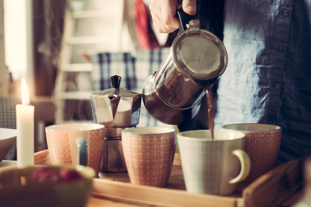 person pouring tea on white ceramic mug using teapot beside moka pot